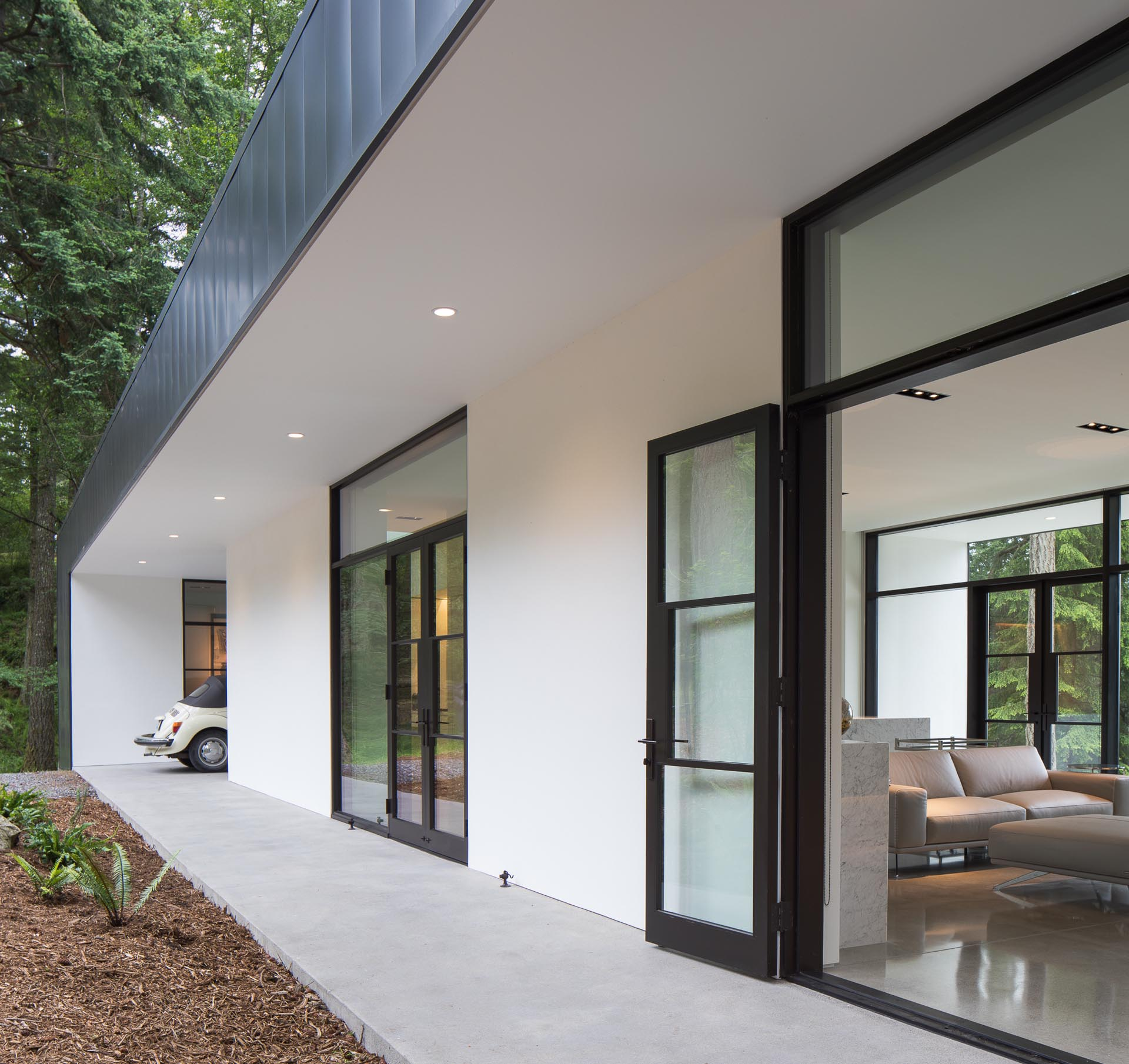 A concrete walkway leads from the carport to the entryway of the home.