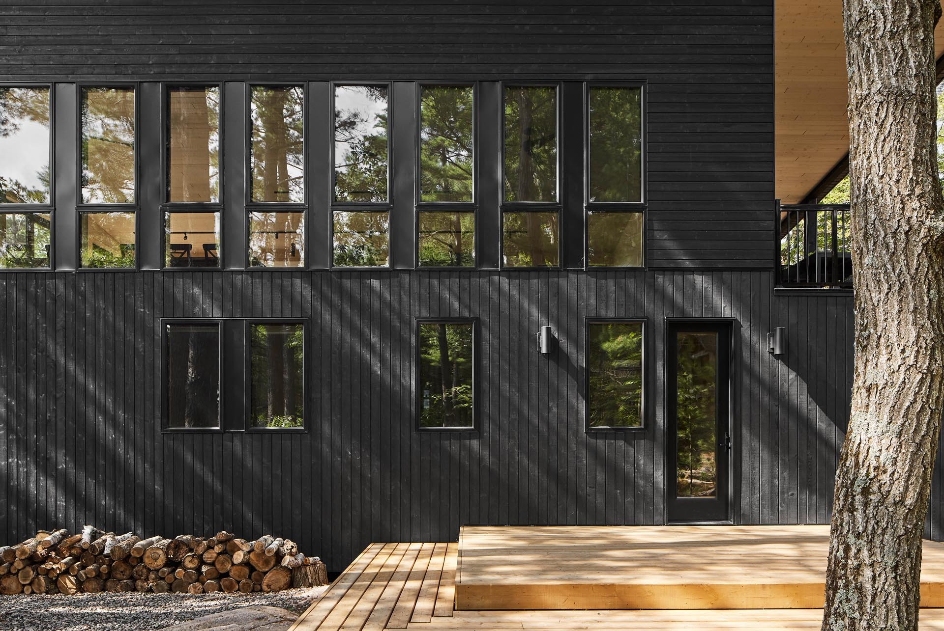 A modern cottage with black wood siding and matching black window frames.
