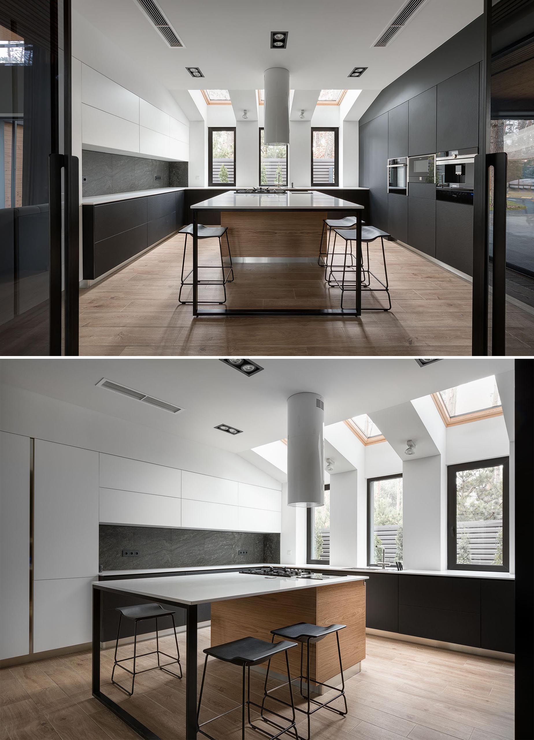 This modern kitchen, which can be opened or closed off to the dining room, includes minimalist, hardware free matte black and white cabinets, as well as an island with a cooktop, and skylights.