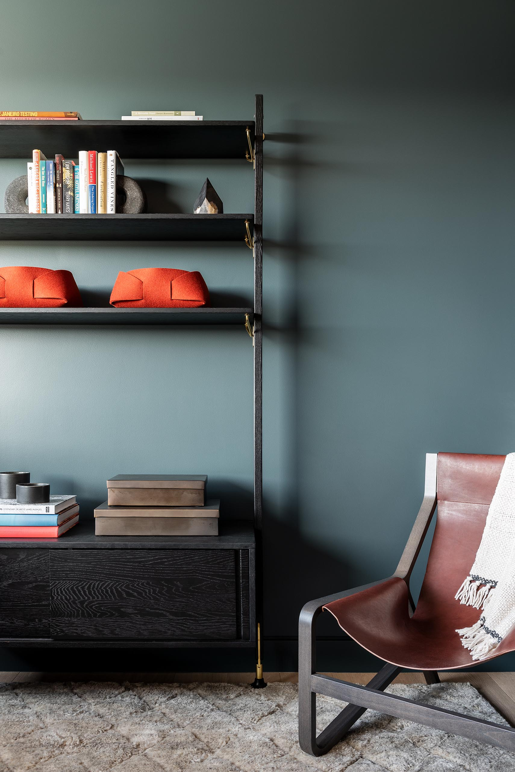 A modern living room with a bold blue-gray accent wall.
