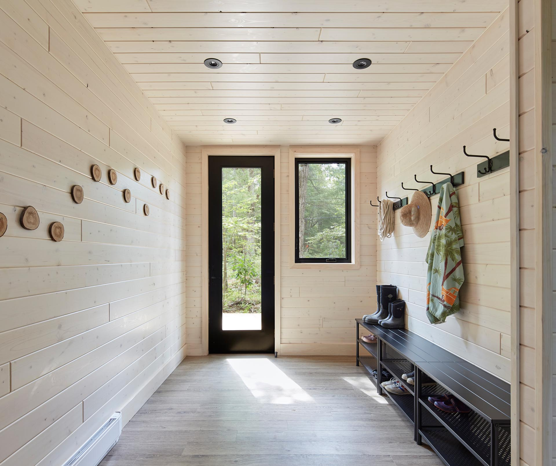 A modern entryway with light wood-lined walls and ceiling, and a matte black bench.