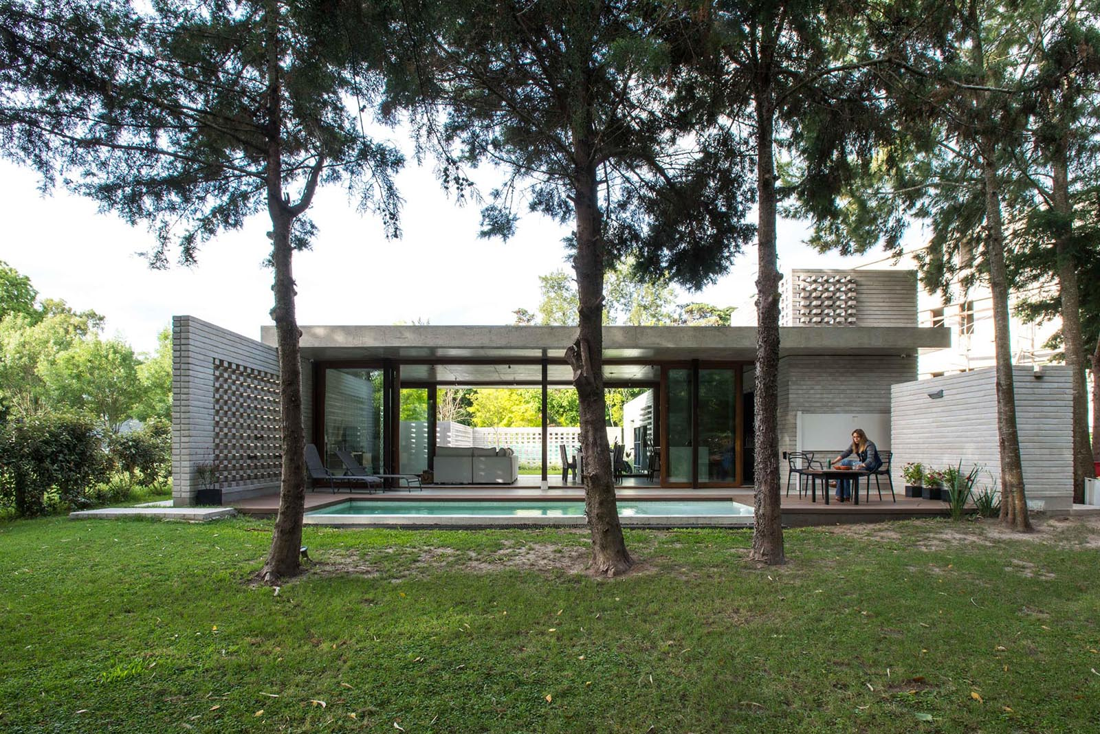 A modern concrete home with a swimming pool and glass walls.