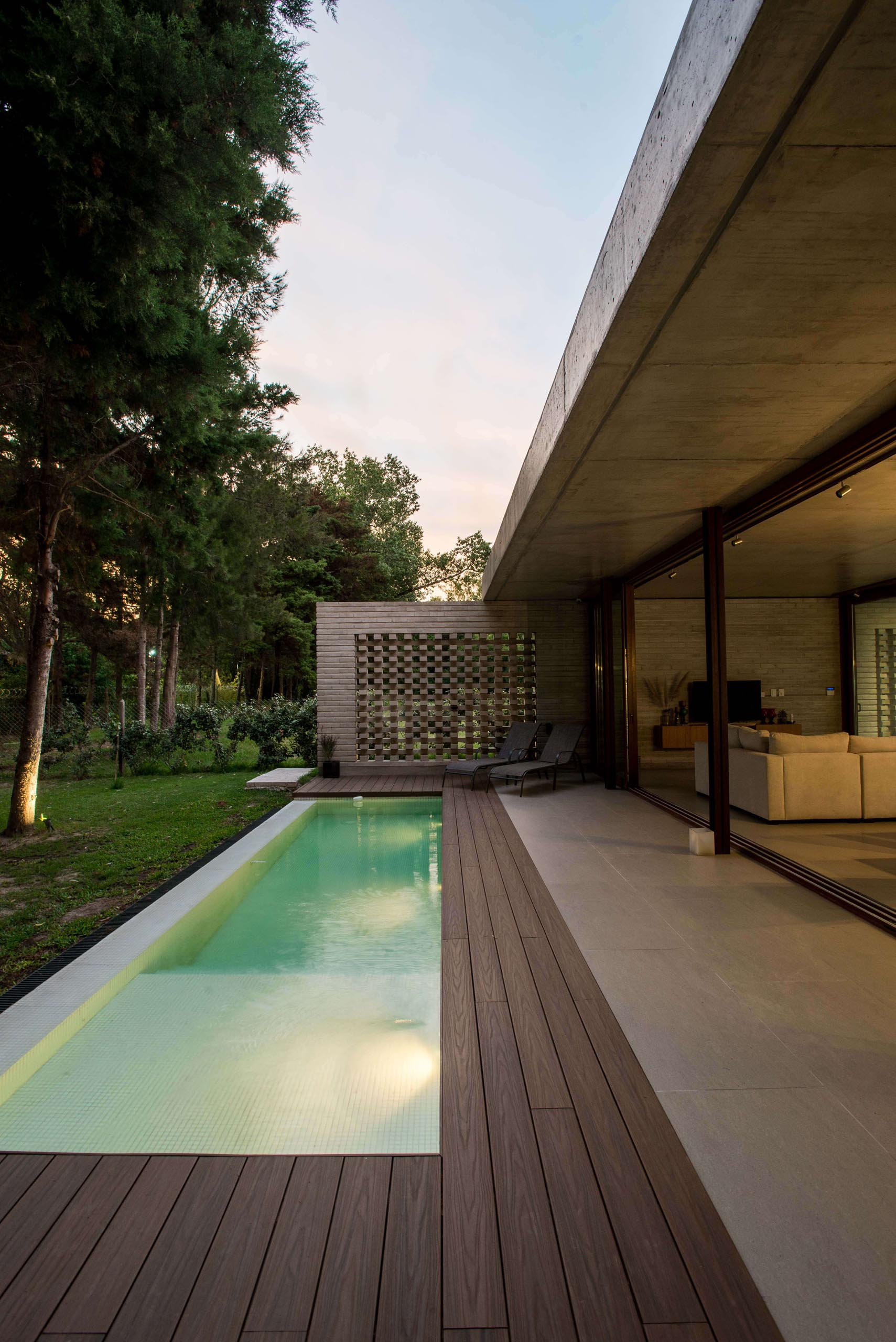 A modern concrete home with sliding glass walls and a swimming pool.