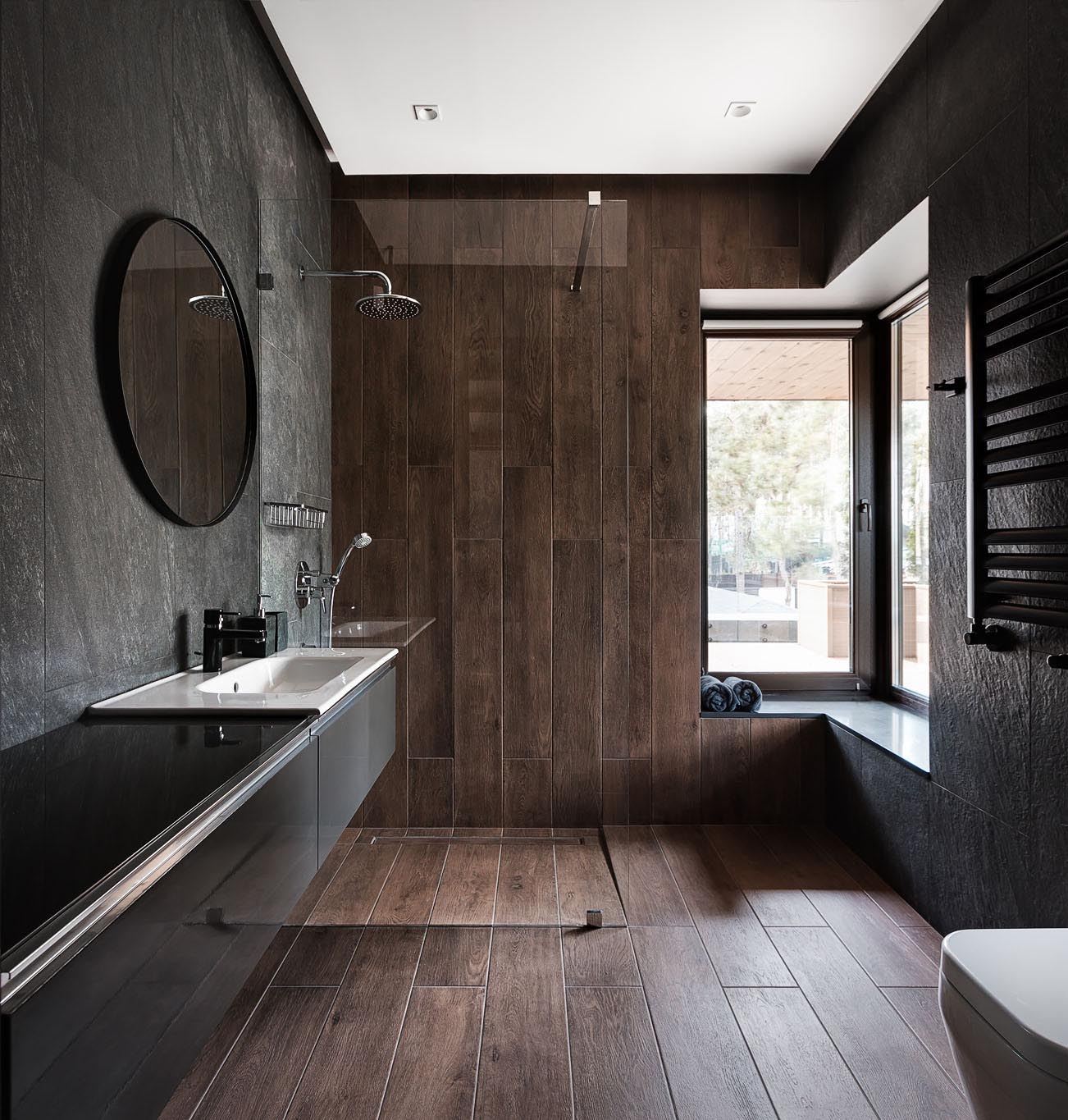 This modern bathroom has a dark material palette with gray walls, wood tiles that travel from the floor to the wall, and a floating black vanity.