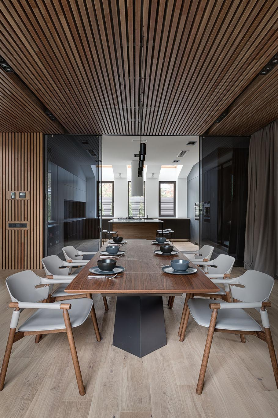 This open concept dining room has a wood slat ceiling, a wood dining table, and dining chairs that match the neutral color palette.