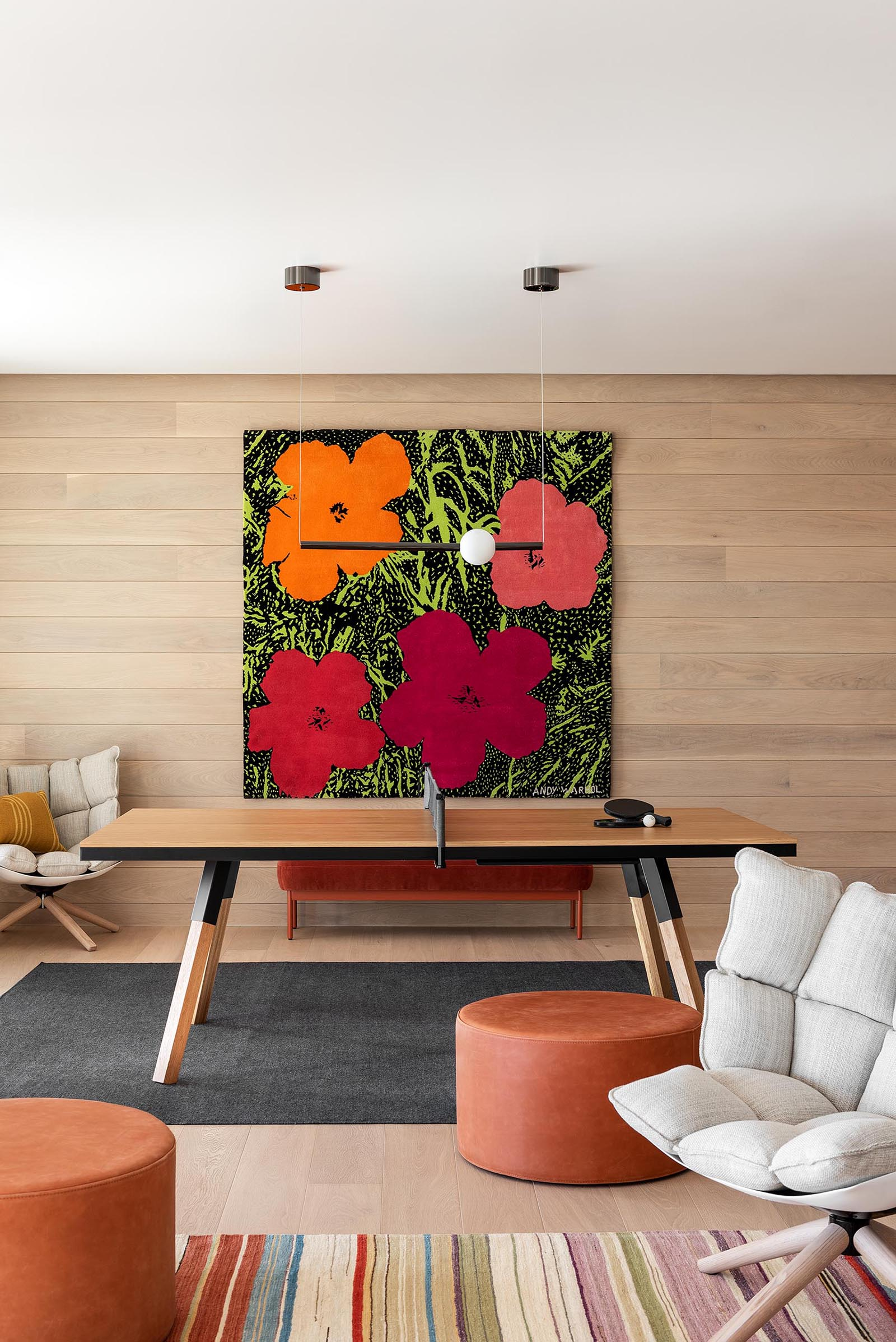 A modern games room with a wood accent wall adorned with a colorful floral art print.