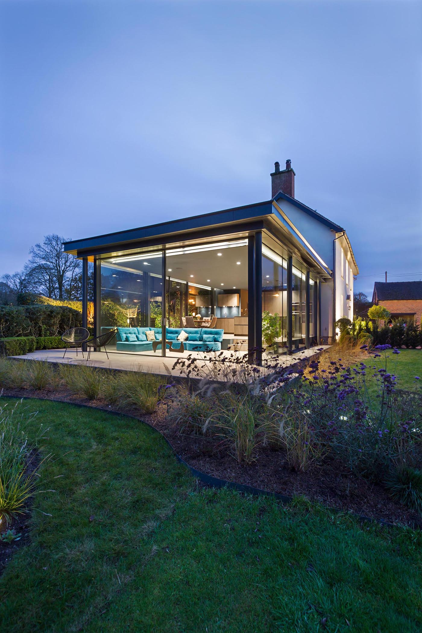 A modern extension with glass walls was added to a heritage home in England.