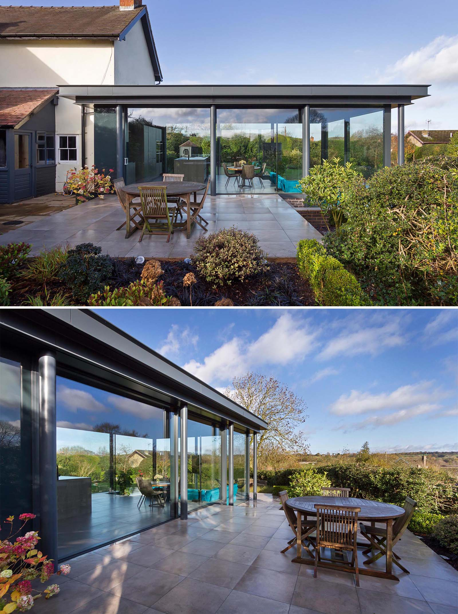 A modern home addition with glass walls has a patio that creates a space for outdoor dining, and connecting with the garden, where there's also an outdoor sofa for relaxing.