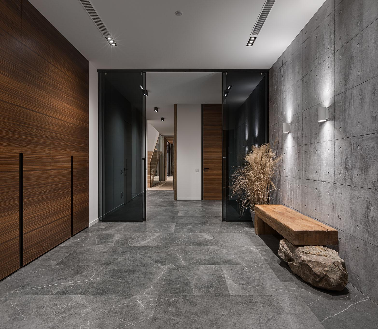 This modern entryway has an exposed concrete wall highlighted by two wall scones, as well as a dark wood wall, and features a wood bench that rests on a boulder.