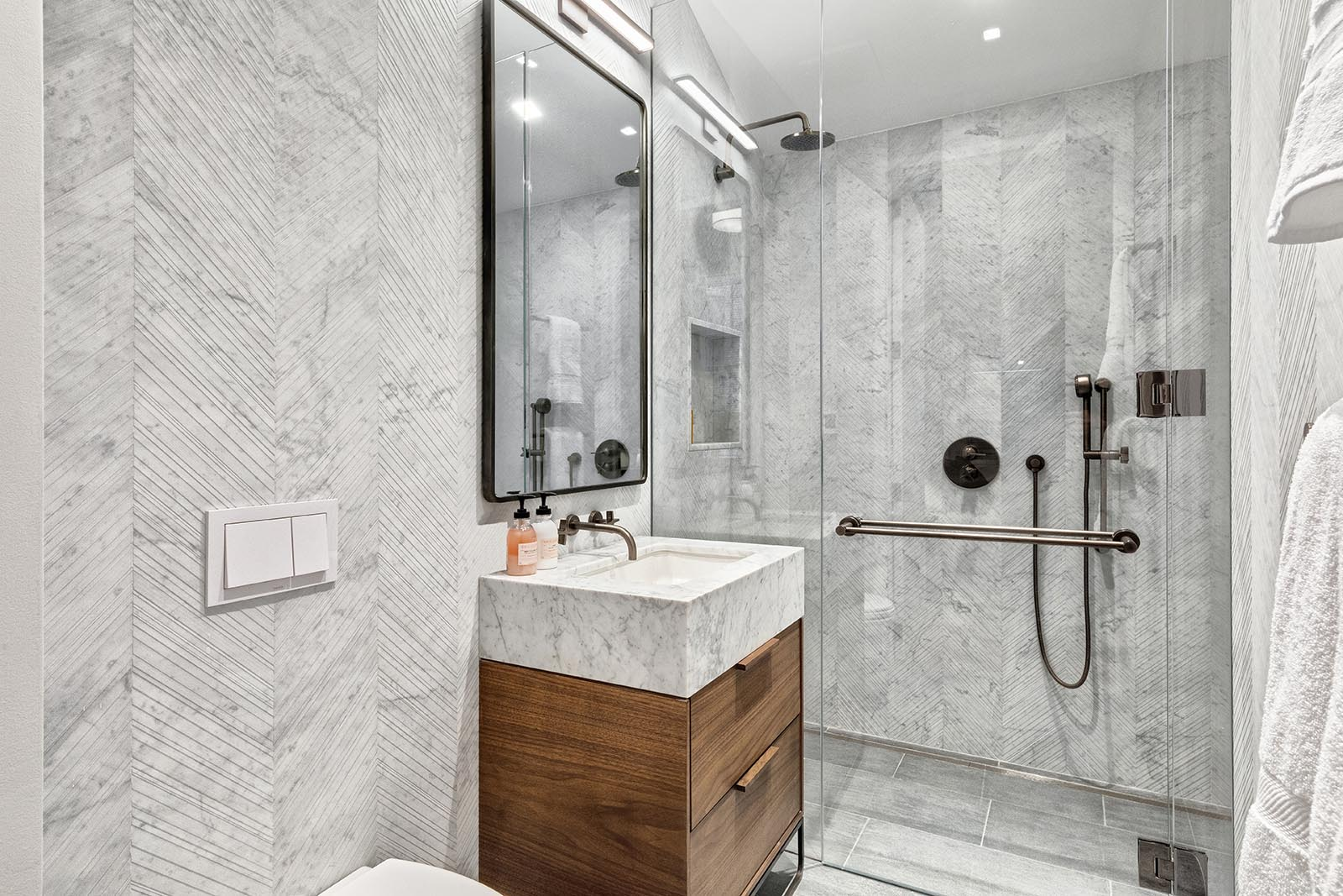 In this modern bathroom, there's floor-to-ceiling gray stone walls, a wood vanity, and a glass enclosed shower.