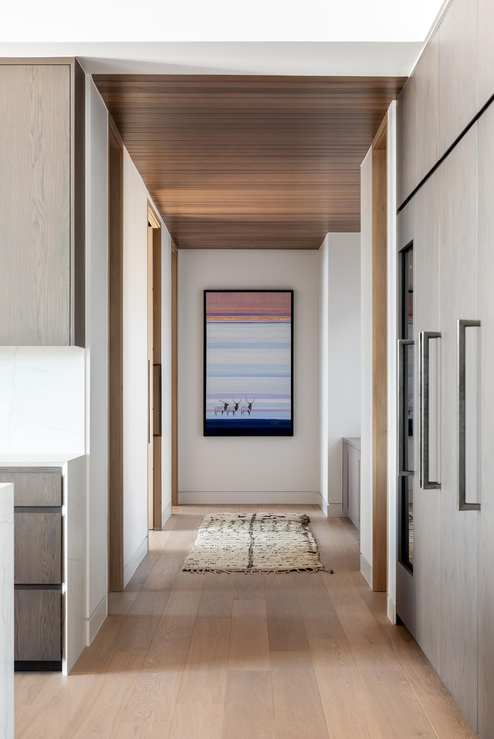 In this modern hallway, the wood ceiling and wood floors add warmth to the interior.