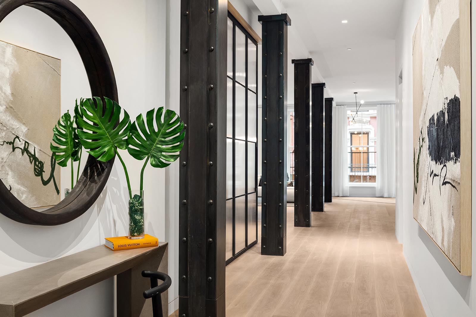 A wide hallway that showcases the steel beams, separates the living area from the sleeping quarters in this modern home.