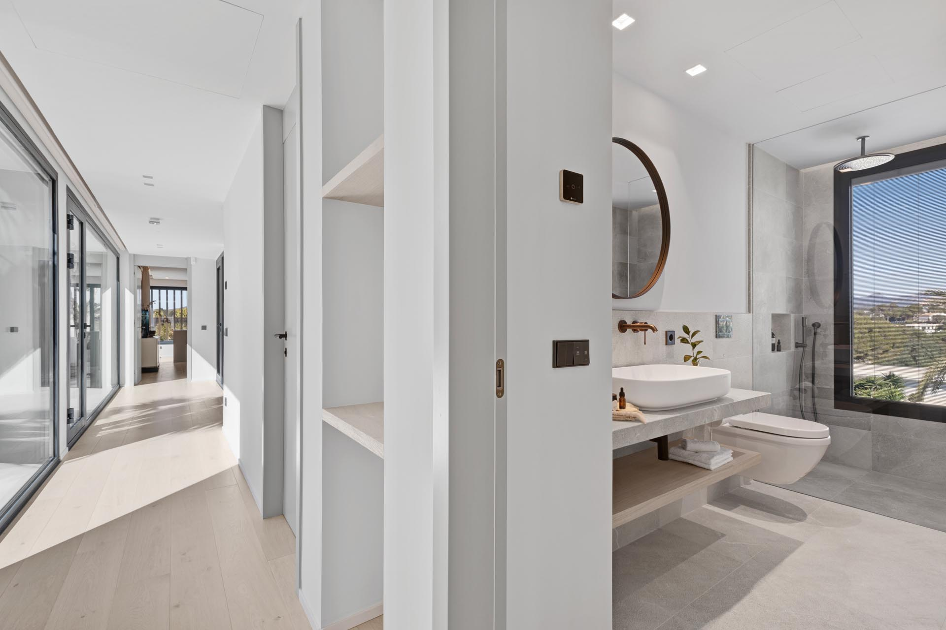 In this modern bathroom, there's a large window that provides tree views from the shower.
