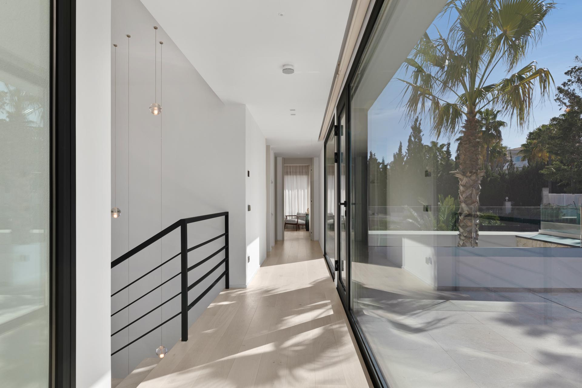The upper floor of this modern house has large windows that provide an abundance of natural light.