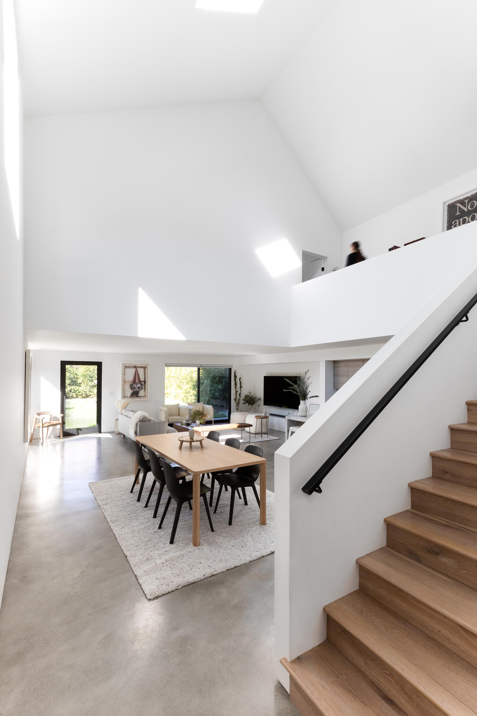 Inside this modern home, there's an open floor plan with the living room, dining room, and kitchen all sharing the same space. Also included are high ceilings, concrete floors, and bright white walls.
