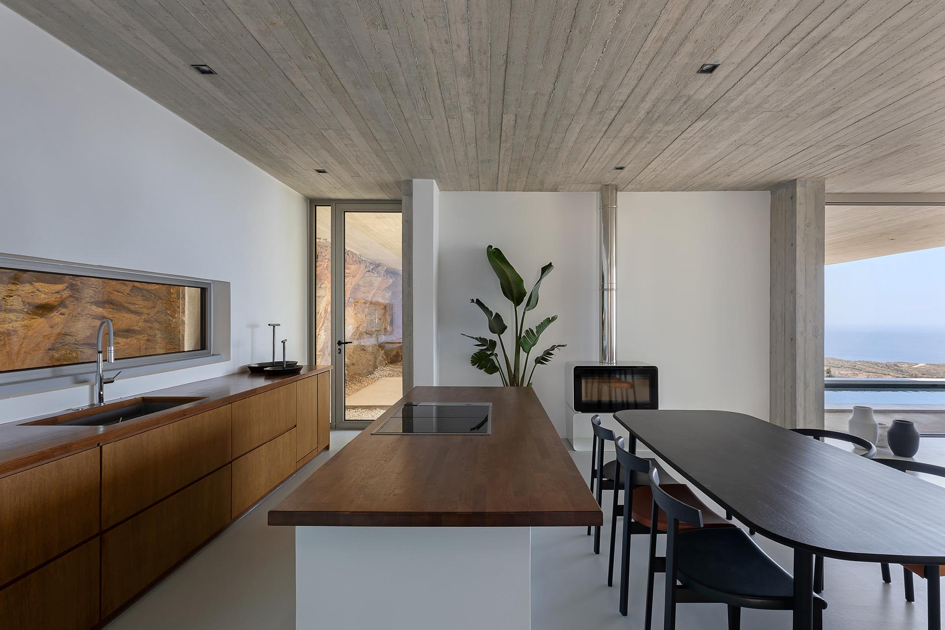 A concrete home built into the hillside, has an open living room, dining room, and kitchen, with the backsplash providing a view of the natural rocks.