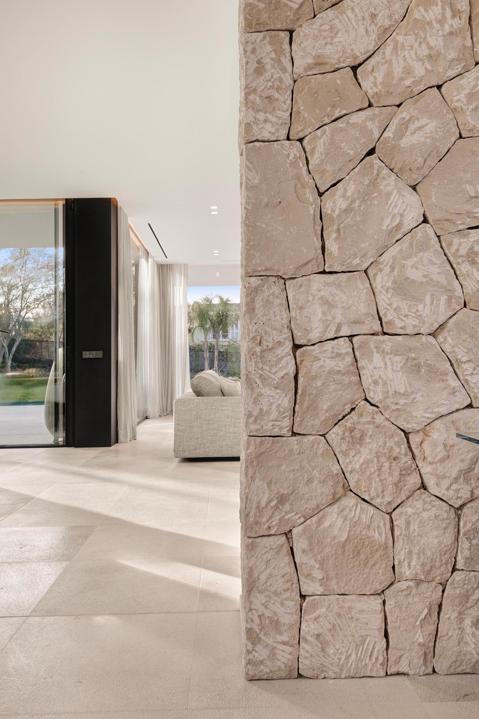 The local dry stone used on the exterior of this modern home, has also been introduced to the interior in the form of accent walls.