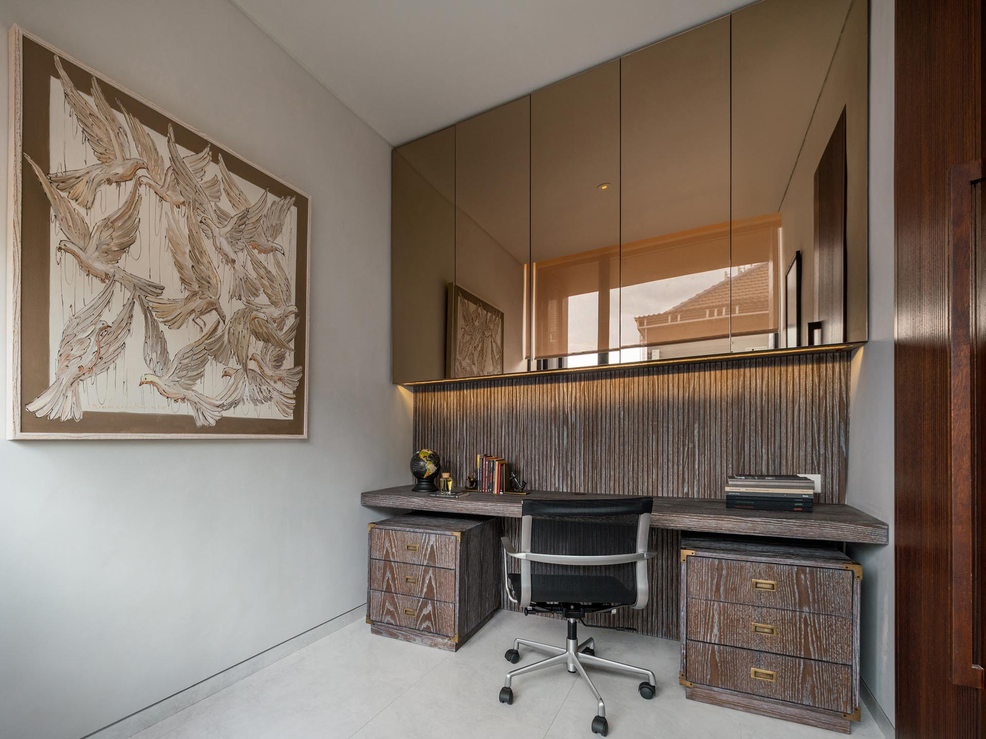 A home office has mirrored cabinets positioned above the desk.