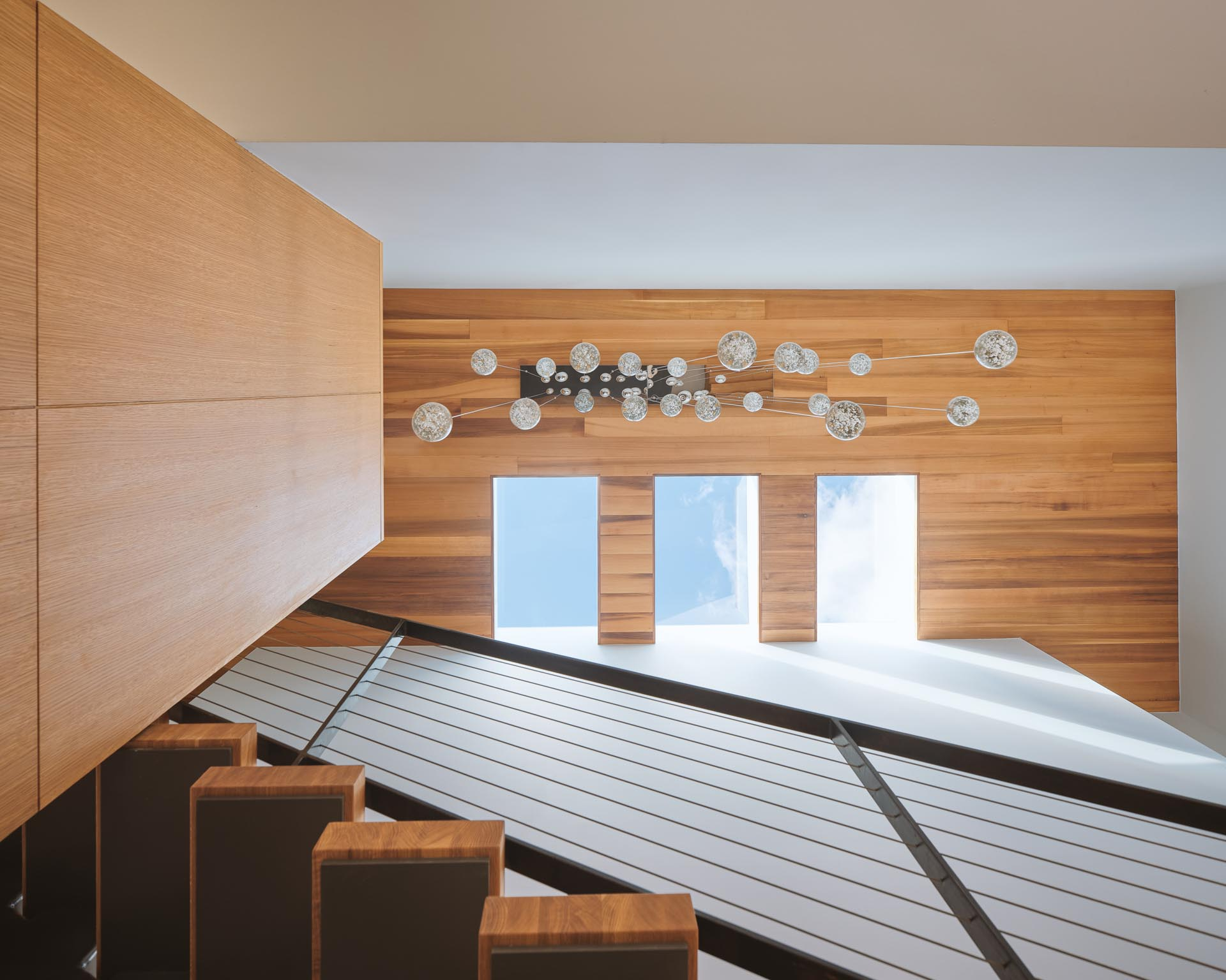 A modern wood ceiling with three skylights.