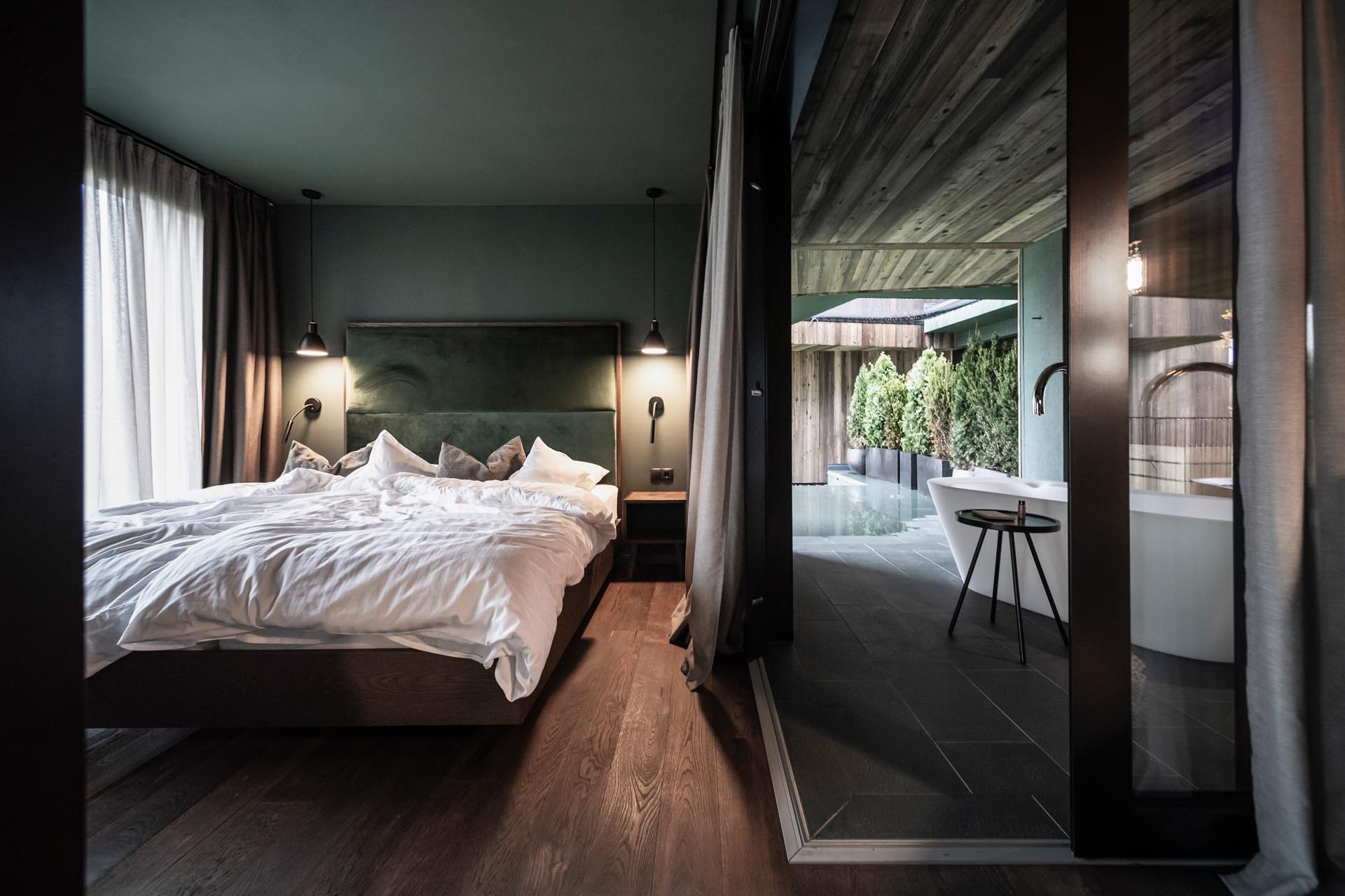 A modern hotel room a glass walled bedroom and outdoor bathtubs.