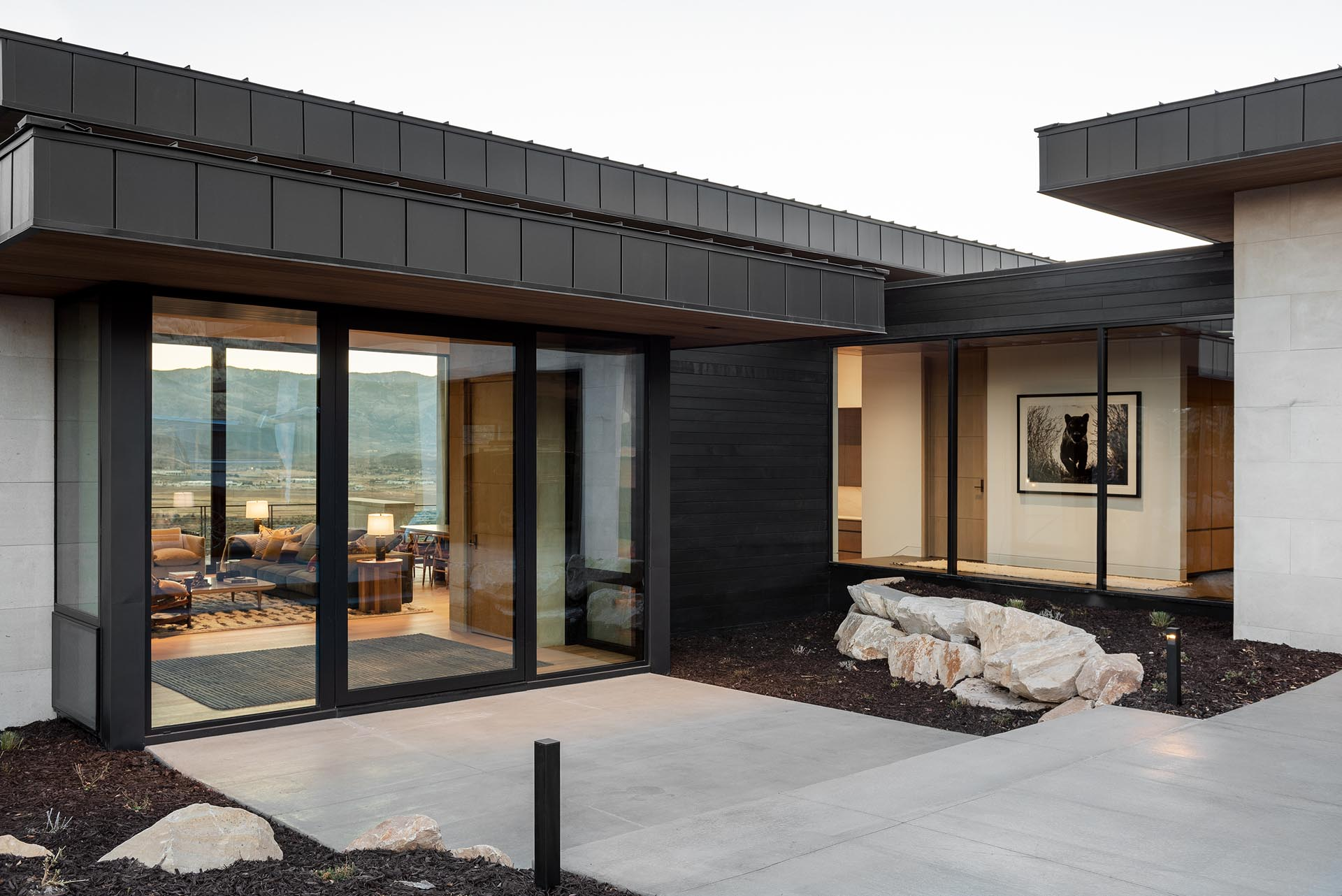 The exterior of this home includes exposed concrete and black siding, while a glass front door gives a glimpse of the interior.