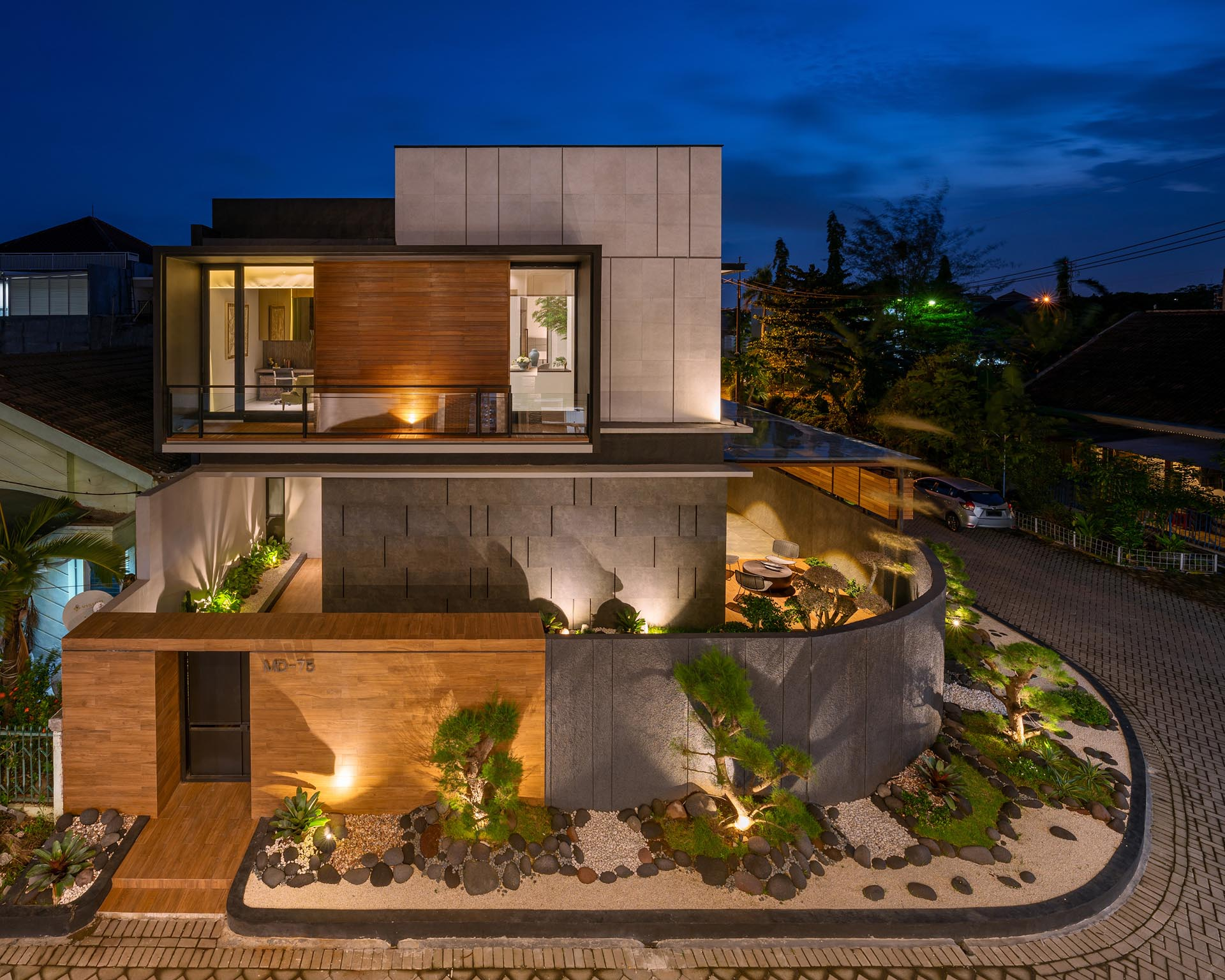 This Zen garden creates modern  curb appeal for a corner lot, and has a dark matte black and wood fence as a backdrop. It also includes ornamental trees, white pebbles, gray stones, and small sections of grass.