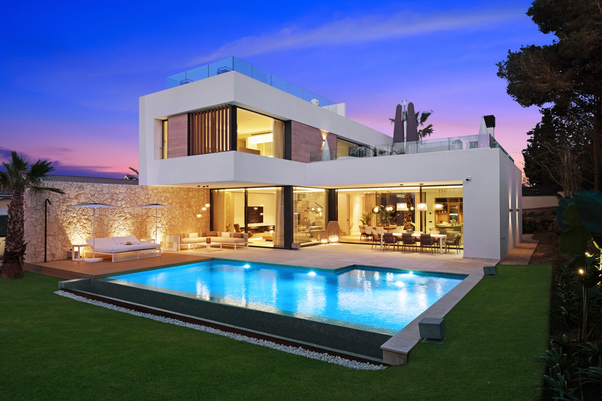 A modern home with stone walls and a swimming pool is designed for outdoor entertaining.