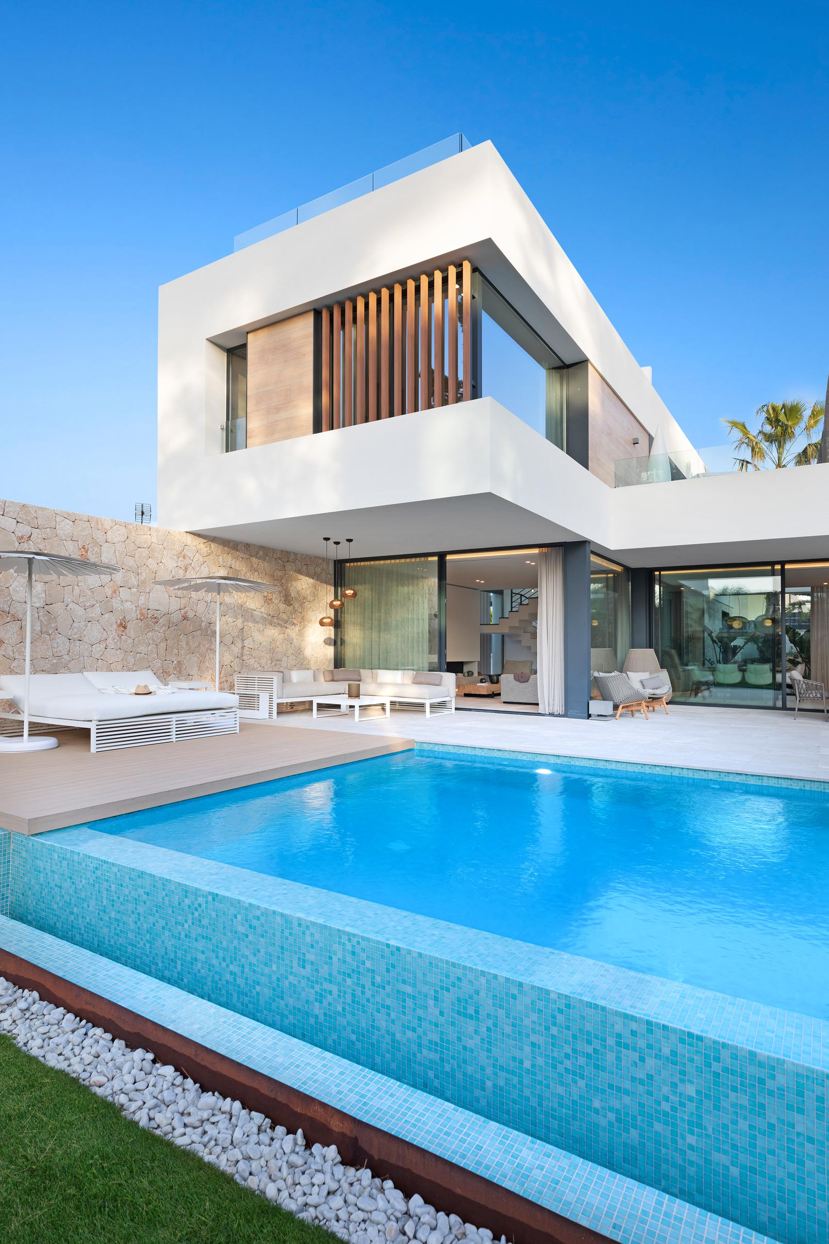 A modern home with a swimming pool, stone walls, a deck, and partially covered patio.