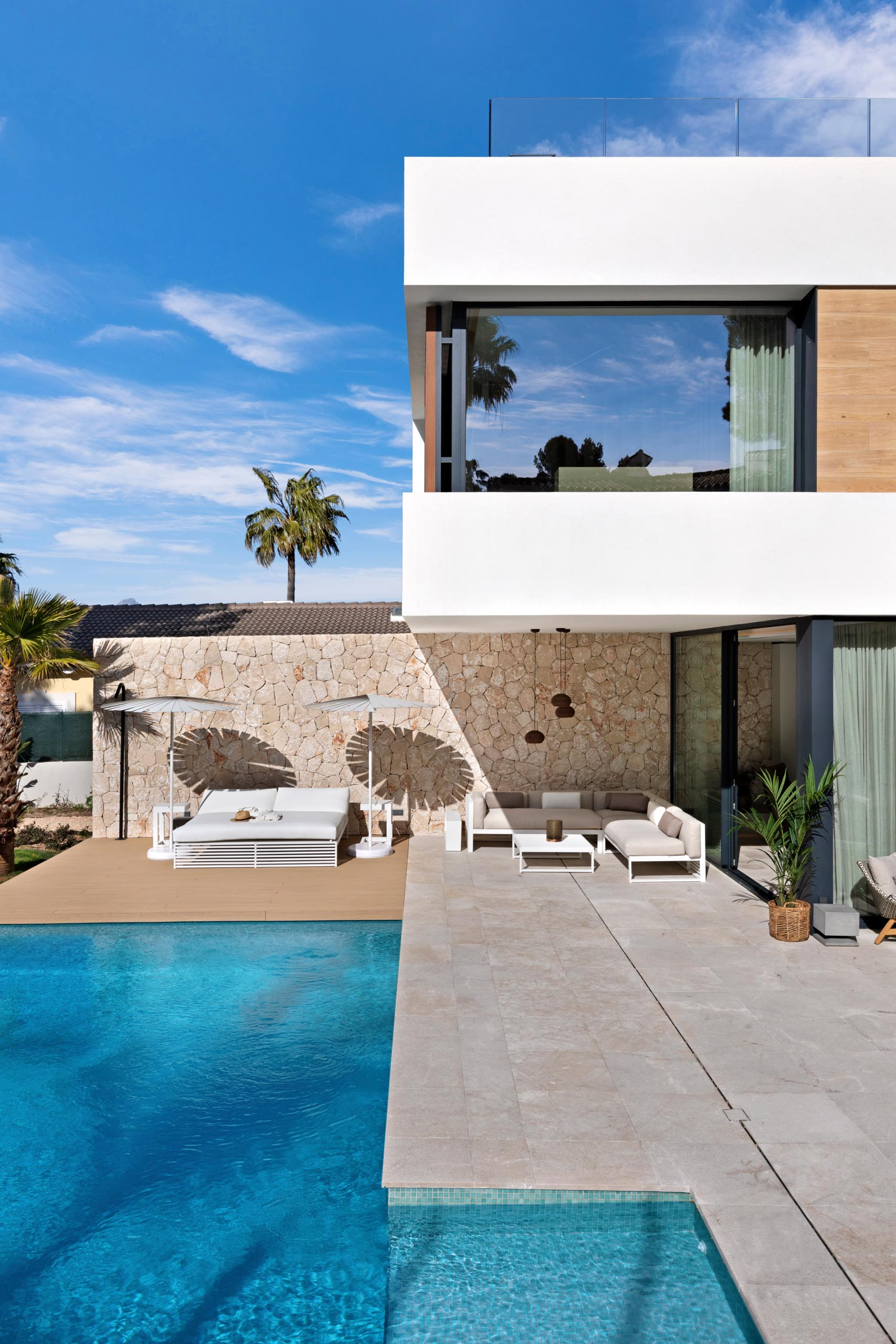 A modern home with a swimming pool and deck, a stone wall, and partially covered patio designed for outdoor entertaining.