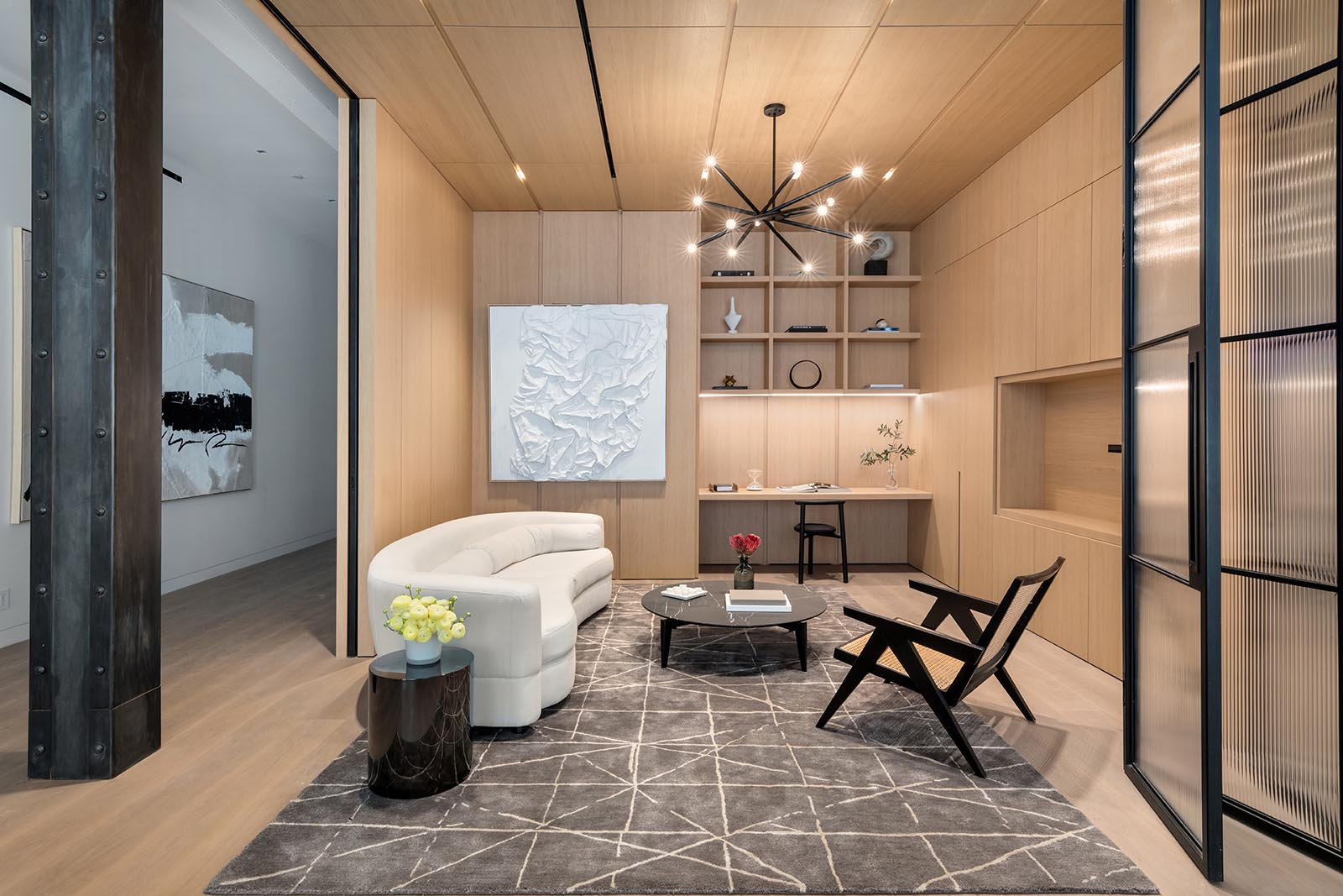 A spacious library with a built-in desk, is clad in millwork that was made in Italy by Canova, and includes floor-to-ceiling glass and steel casement folding doors, creating an open and versatile additional living space.