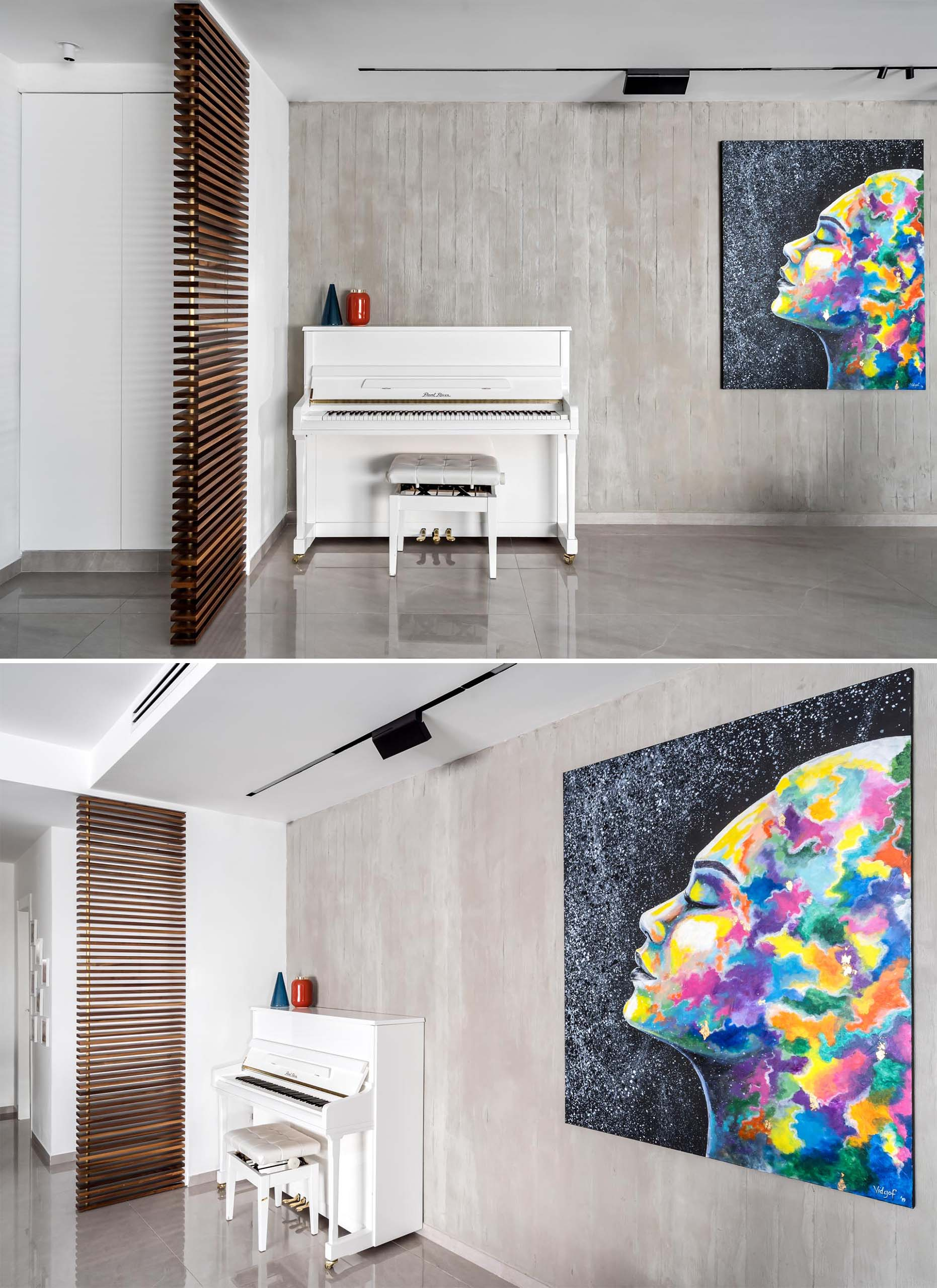 An exposed concrete wall decorated with a bold and colorful art piece.