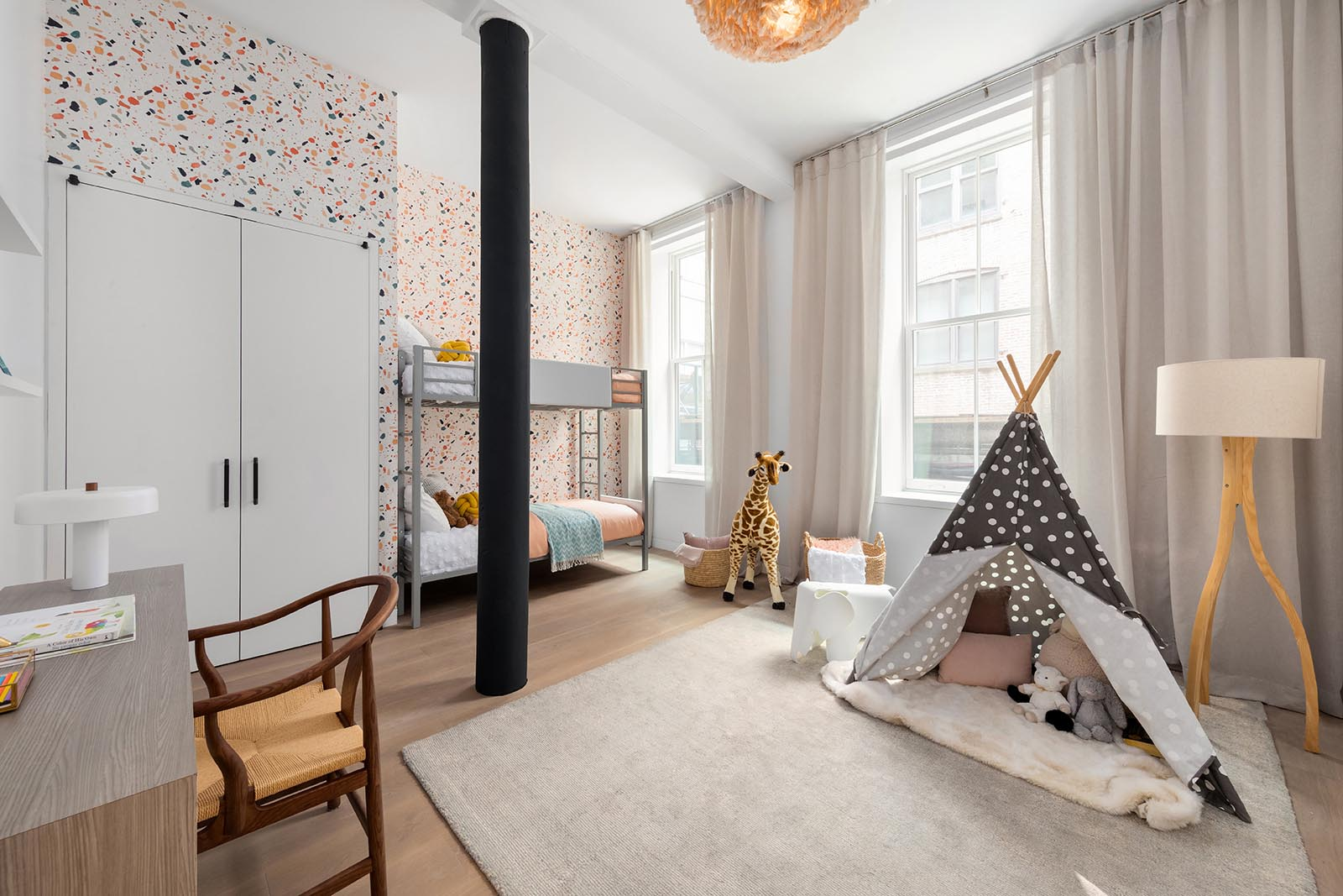 In this modern kid's bedroom, colorful wallpaper has been used to create a fun backdrop for the bunk beds, while the open space has been designated as a play area.