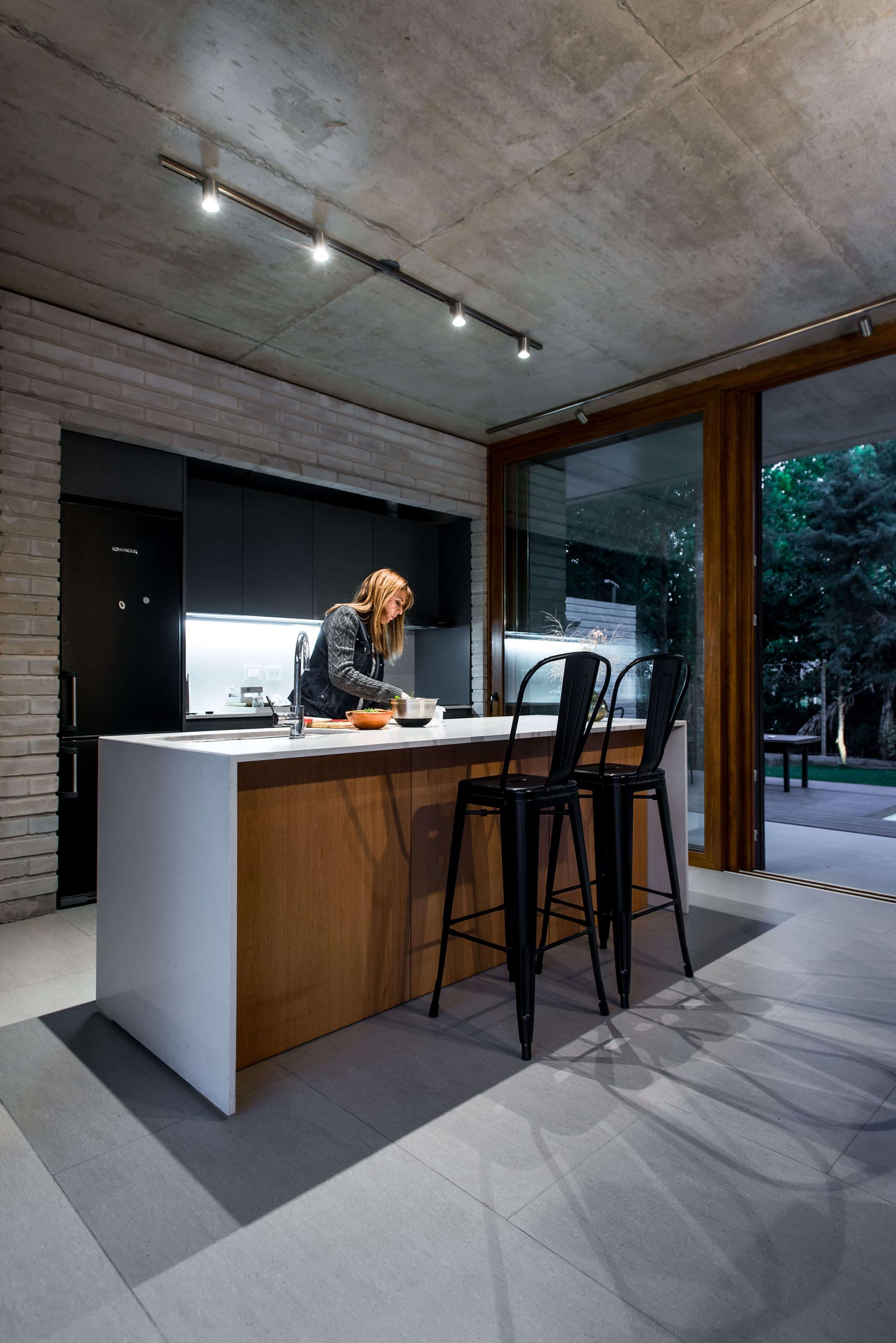 A modern kitchen with exposed concrete, black cabinets, a white island and wood accents.