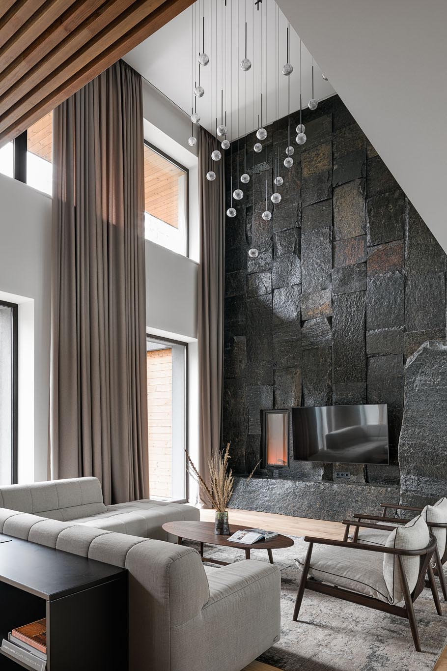 In this modern living room, there's a double height ceiling with a sculptural light installation, and a large, dark, and monumental natural stone boulder wall that's used as a backdrop for the fireplace and television.