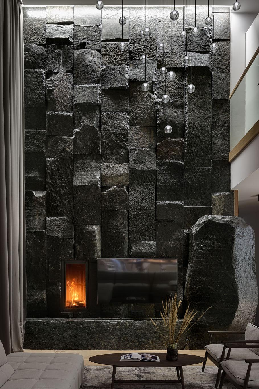 A large, dark, and monumental natural stone boulder wall that's used as a backdrop for the fireplace and television.