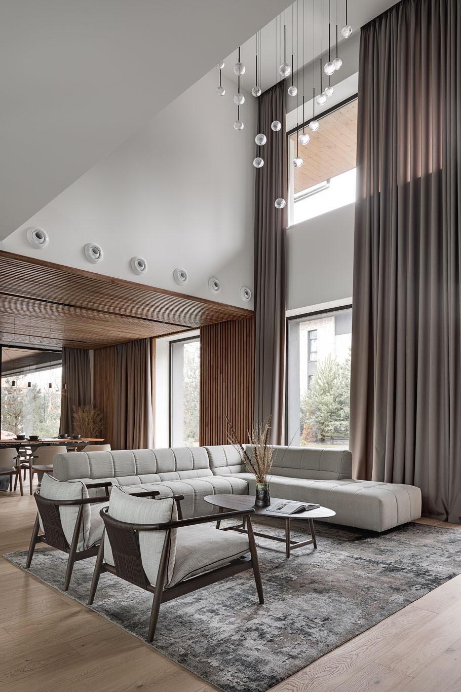 In this modern living room, there's a double height ceiling with a sculptural light installation.