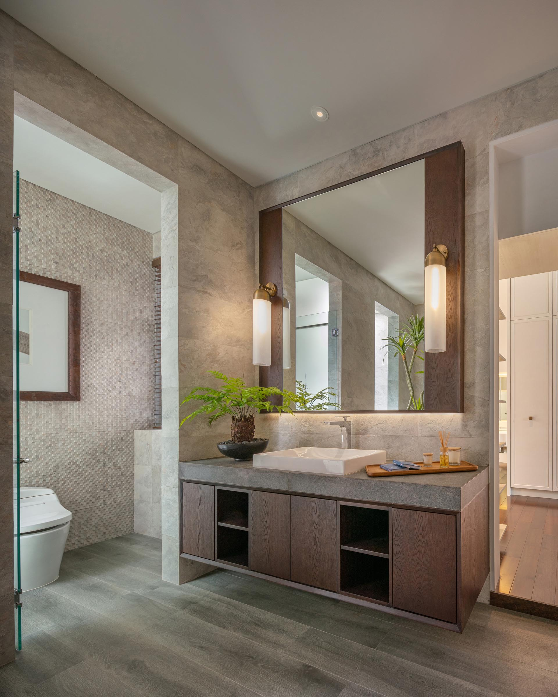 In the ensuite bathroom there's a floating wood vanity with a thick concrete countertop and a freestanding bathtub. Off to the side are separate rooms for the toilet and shower.