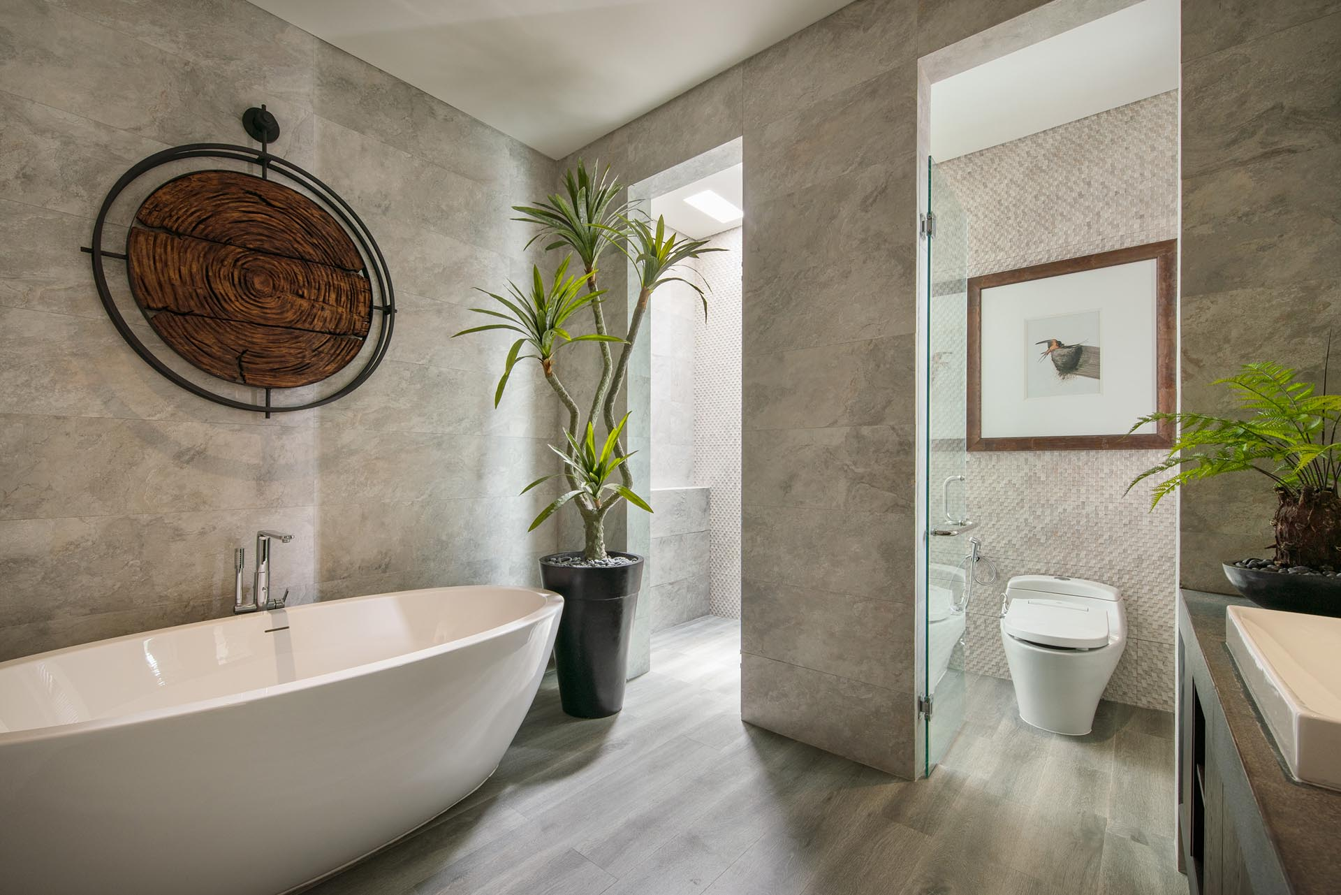 A modern bathroom with a freestanding bathtub and floor-to-ceiling tiles.