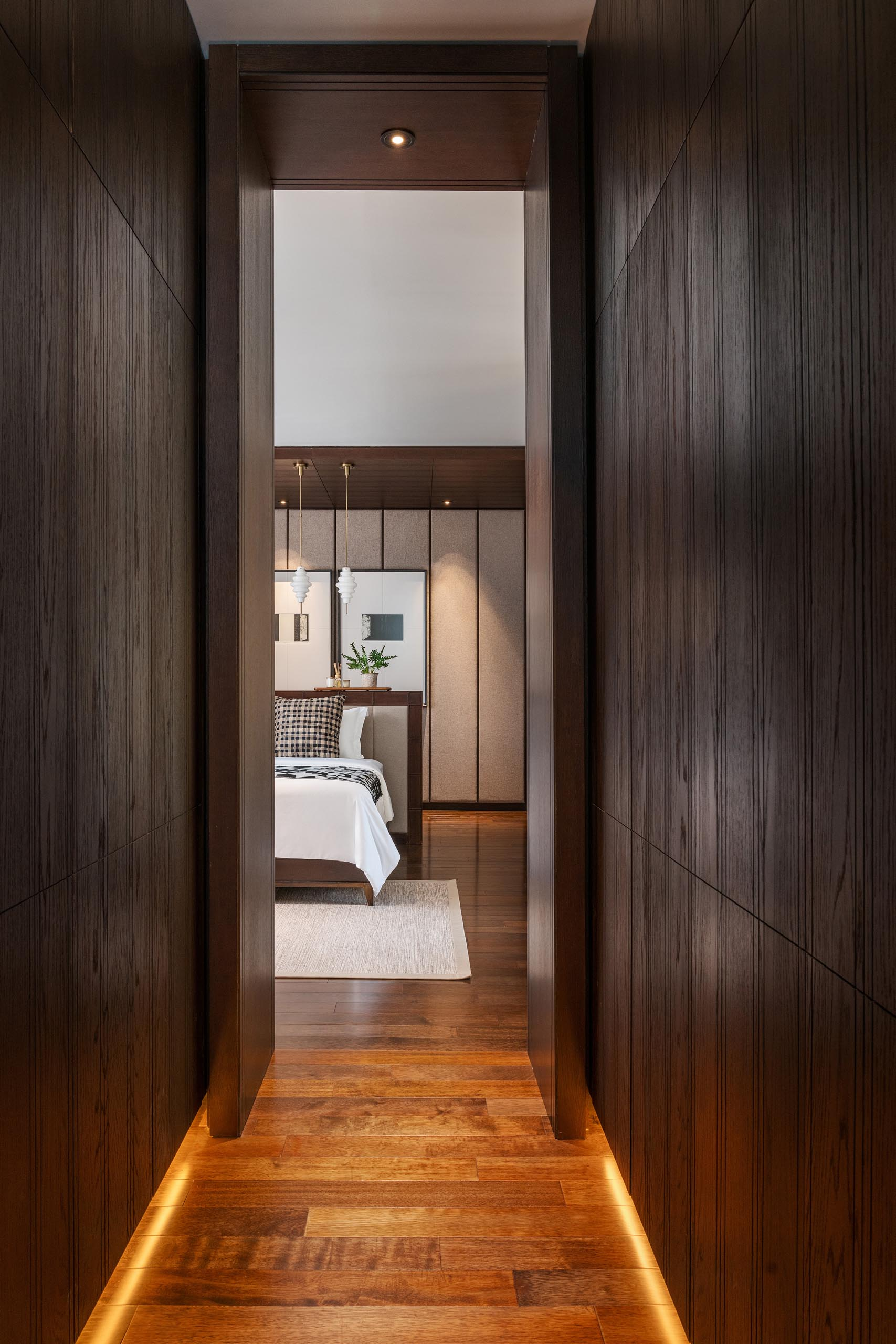 A hallway lined with dark wood cabinets and hidden lighting provides access to the primary bedroom.