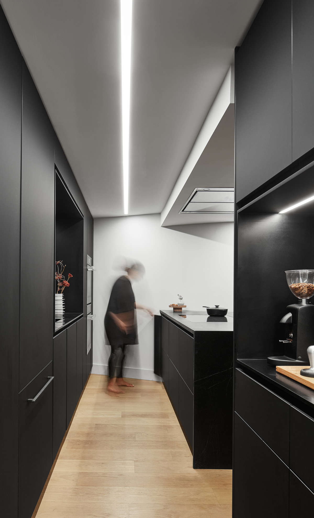 A modern matte black kitchen with hardware free cabinets, a large island, and a coffee station.