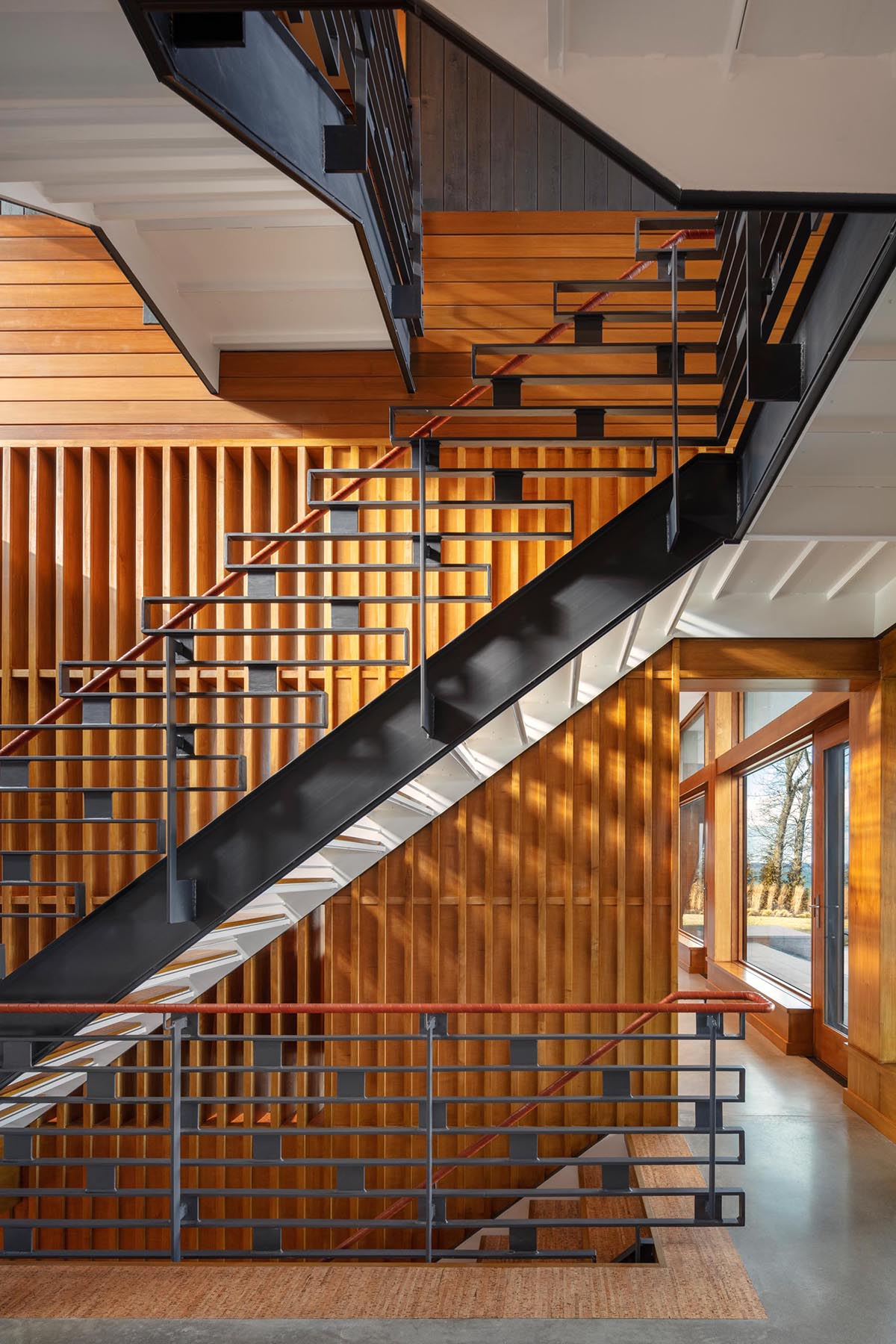 This modern staircase has a decorative metal railing as well as a leather wrapped handrail.