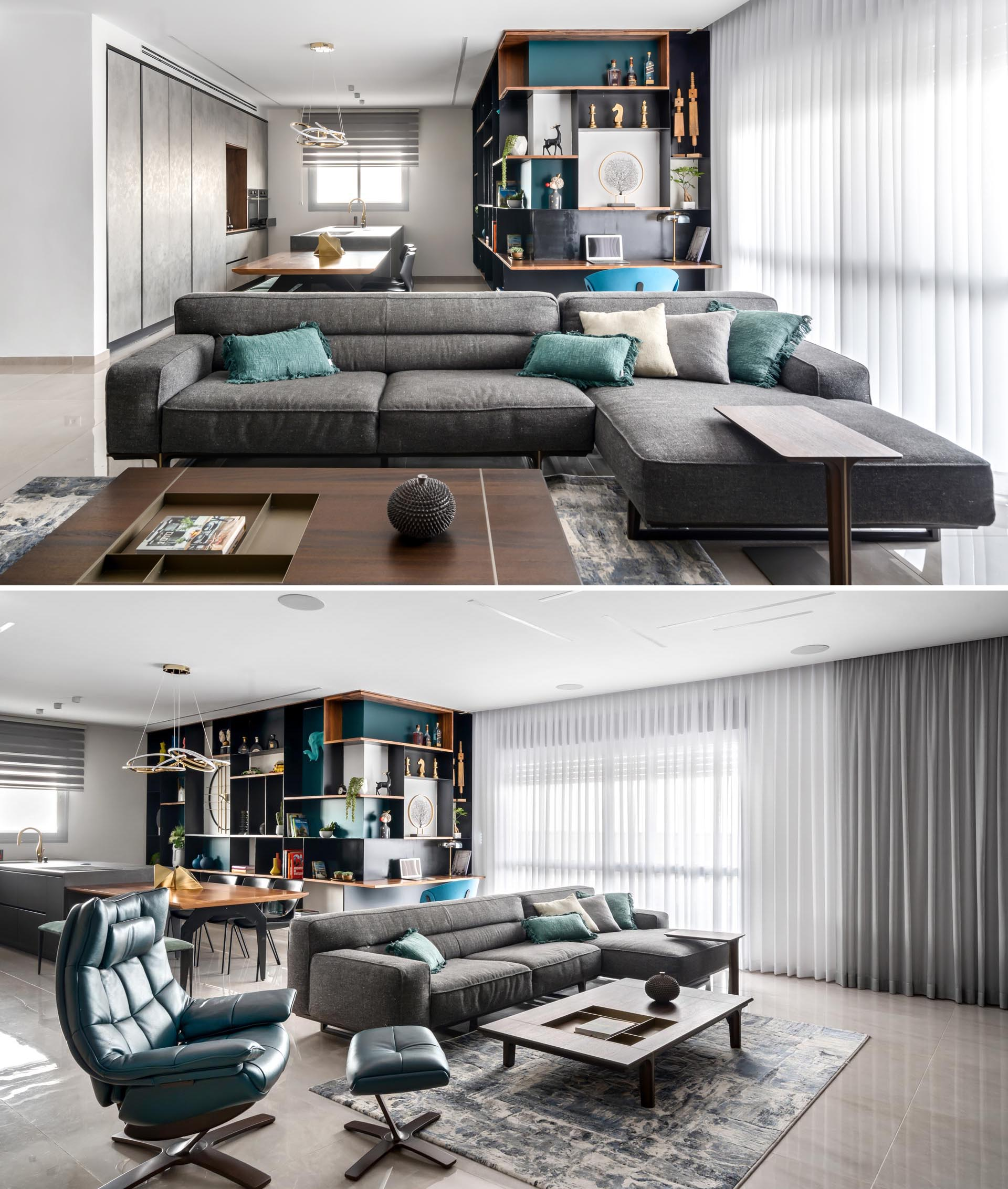 One of the key design elements in this apartment is the inclusion of an entire wall that's filled with steel and wood shelving, and has pop of turquoise adding a colorful accent to the open plan interior.