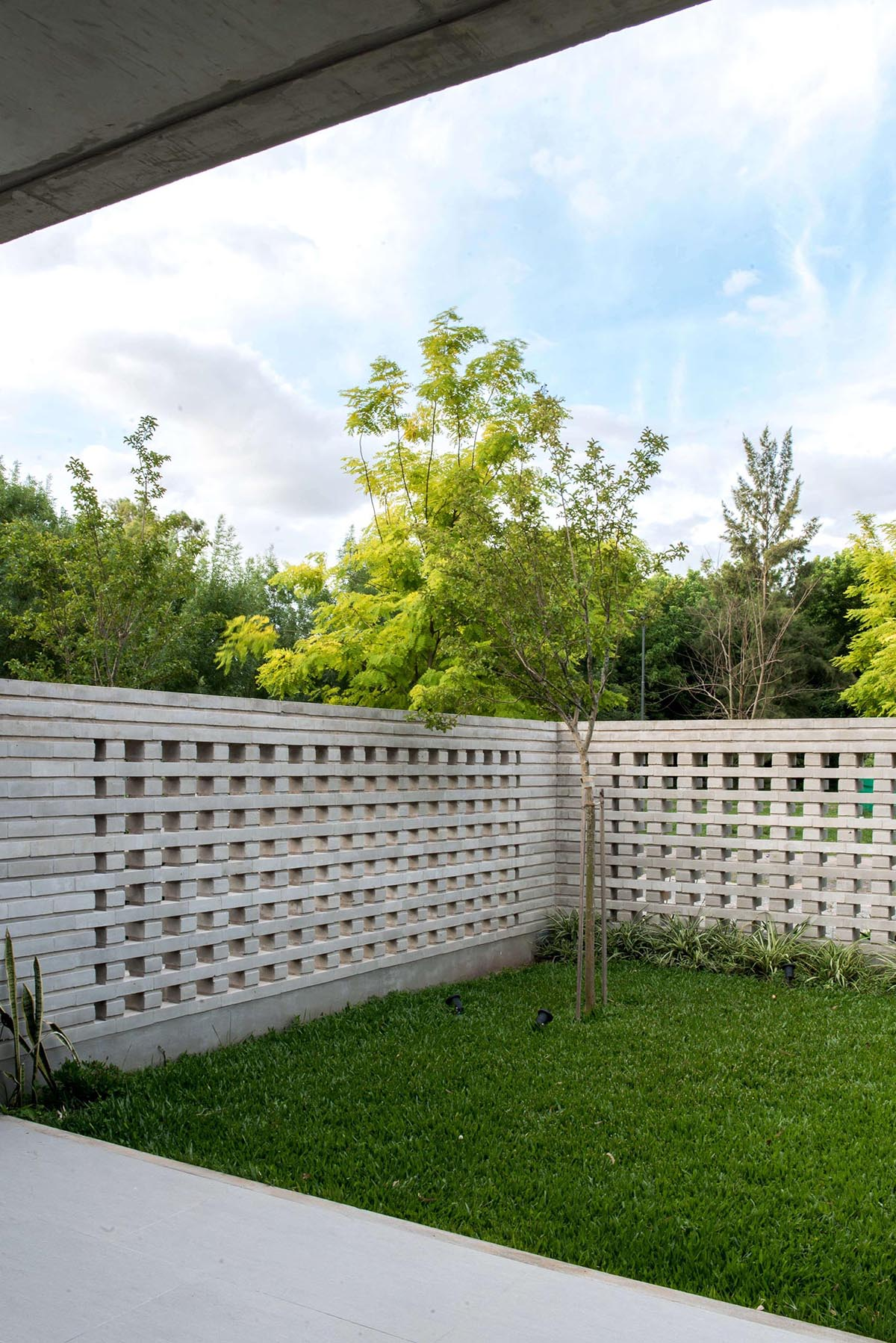 A closeup look at a modern concrete block fence that provides privacy for a home.