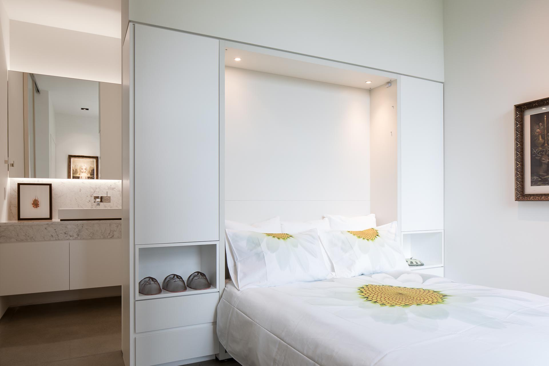 In this modern white bedroom, custom cabinetry surrounds the headboard of the bed, and separates the sleeping area from the en-suite bathroom.