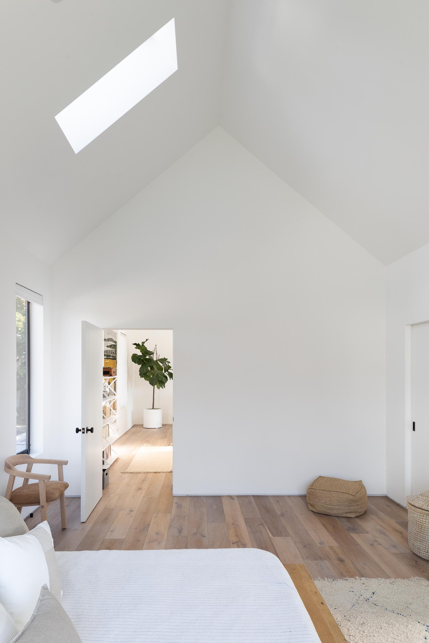 In this modern bedroom, a vaulted ceiling with a skylight makes the room feel large and open, while a wood bed frame and side tables add warmth to the space, and a window seat creates a cozy place to read a book and take in the views of the yard.