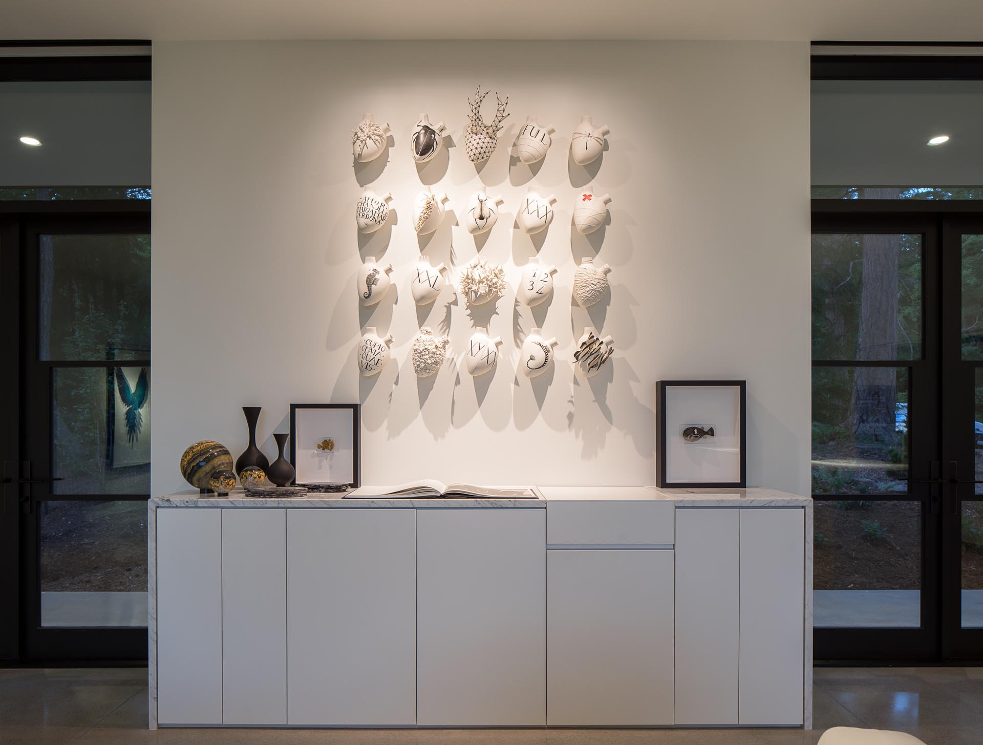 Along the wall in this modern home is a custom-designed cabinet with artifacts, and books, while above, lighting highlights the art.