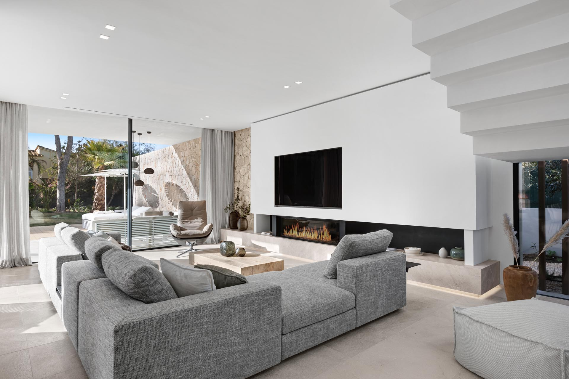 In this modern living room, the L-shaped gray sofa is focused on the linear fireplace with the TV above it. Underneath, there's a Balearic gray limestone hearth with hidden lighting that highlights the floor.