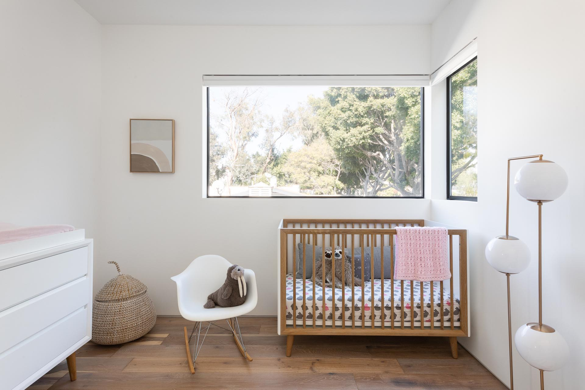 A nursery with large windows and simple yet modern furnishings.