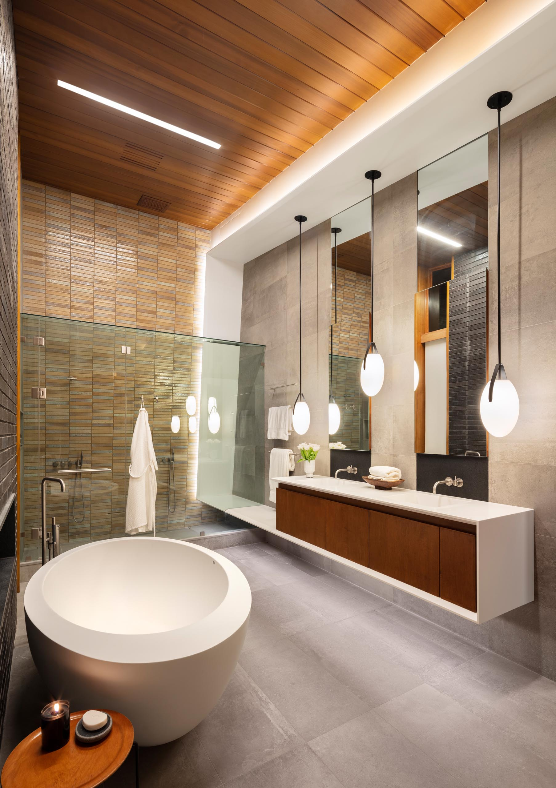 In this modern bathroom there's high ceilings, a freestanding bathtub, and a vanity with three pendant lights hanging above it.