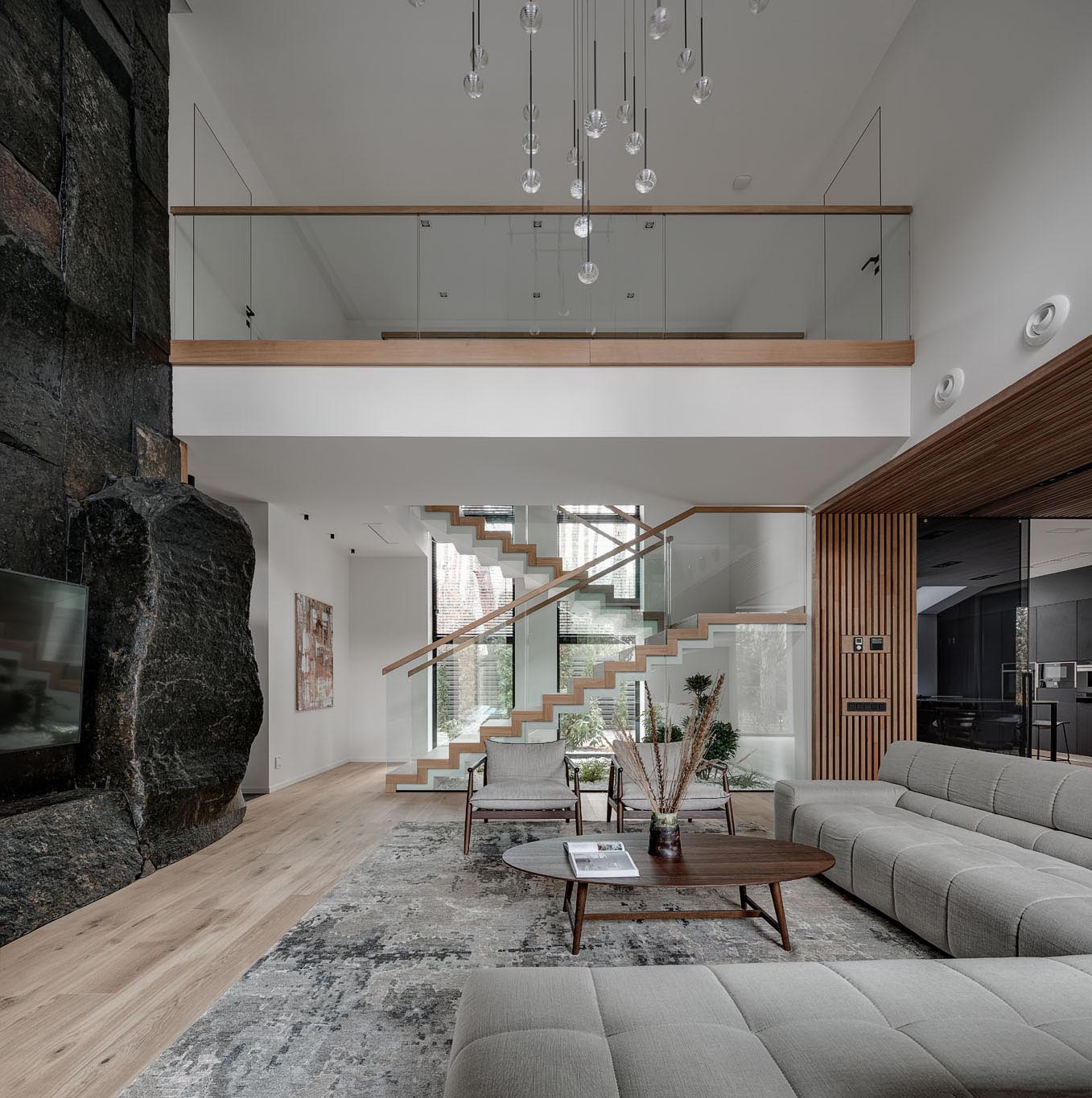 These modern stairs that connect the various levels of the home are made of concrete, wood, and glass. Underneath the stairs, live indoor plants and rocks have been used to create a small garden, bringing the outdoors in.
